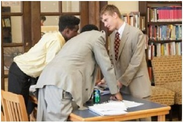 """Ben Speckmann   Eugene Murawski (right) consults fellow """"defense lawyers"""" Andrew Taylor (left) and Quinton Karamoko during a mock trial Thursday. The event was the culmination of a six-week class sponsored by Winston & Strawn LLP to teach legal basics to 15 students at the Midtown Center."""