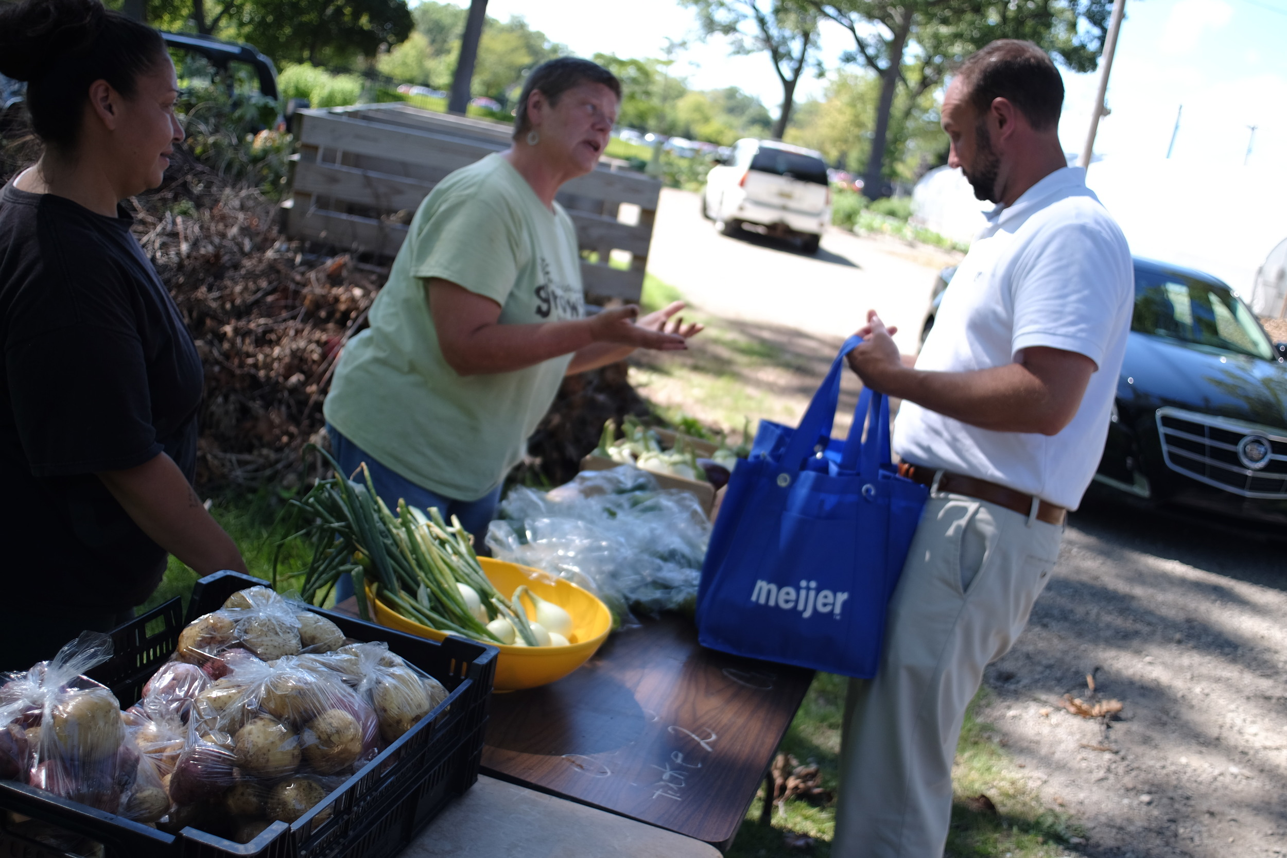 Laurie Wieschowski the farm manager, helps a CSA participant choose their weekly organic veggies at the Mercy Hospital Hackley Campus farm site.
