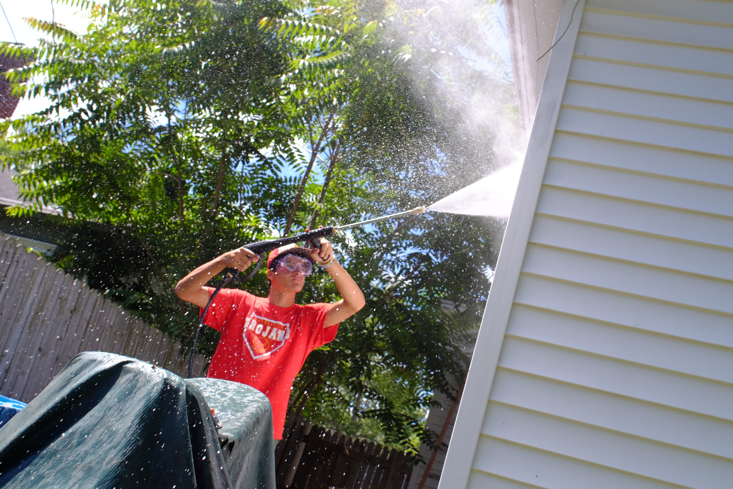 Volunteer from Catholic Heart work Camp cleaning siding on 4th street.