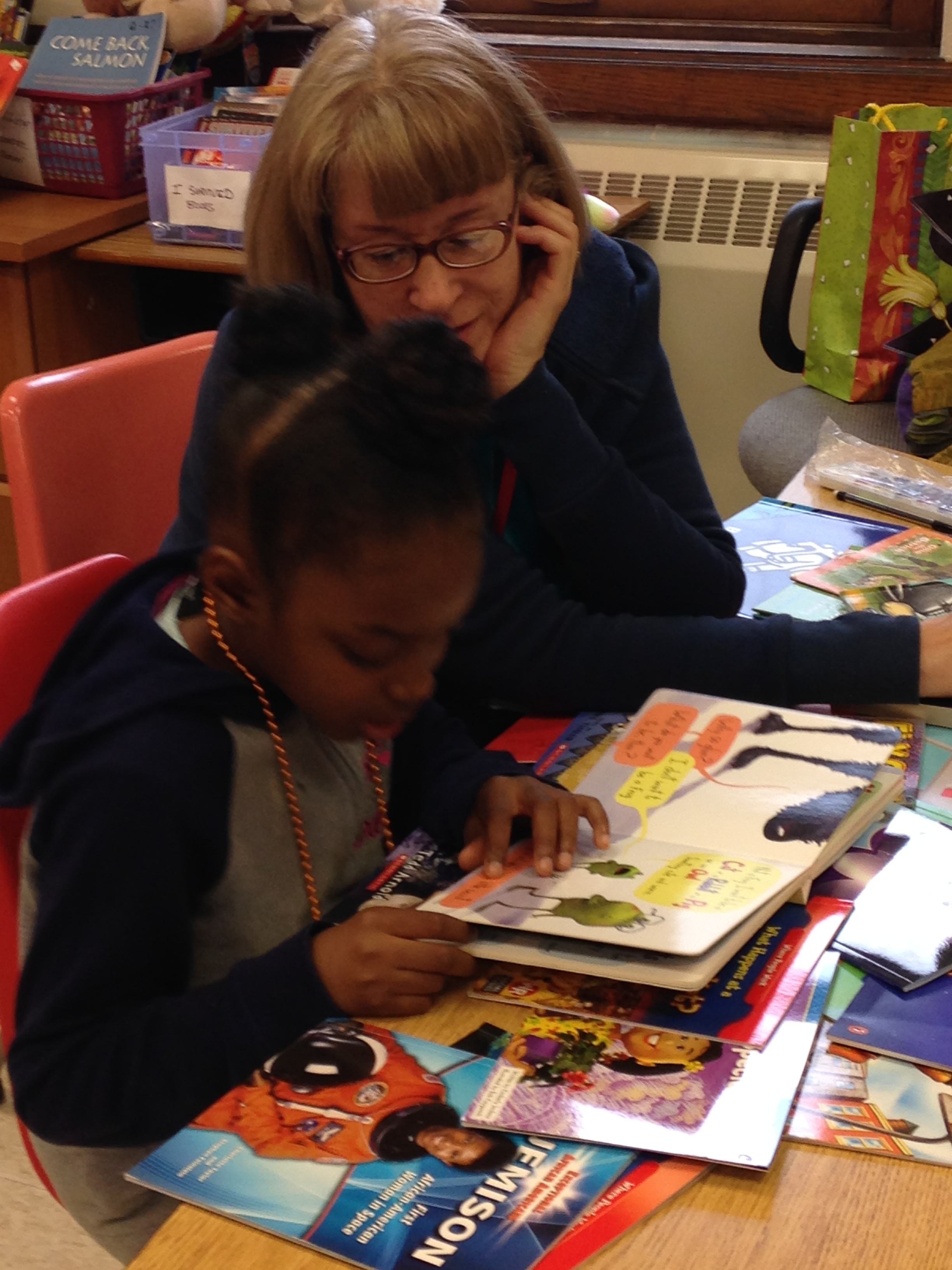 Reading Buddies volunteers work one on one with a partisipants to help build their reading confidence.