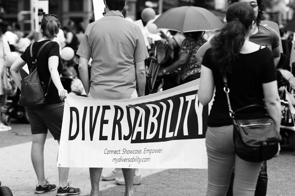 Black and white image of Diversability flag carried by two individuals.