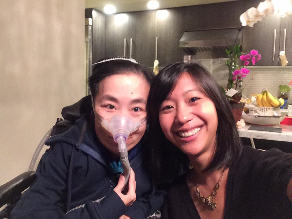 Image description: two Asian American women next to each other at a kitchen table. The woman on the left [Alice] is in a wheelchair with a mask over her nose and wearing a navy blue hoodie. The woman on the right [Tiffany] has a necklace and a black v-neck shirt on. Both are smiling to the camera.