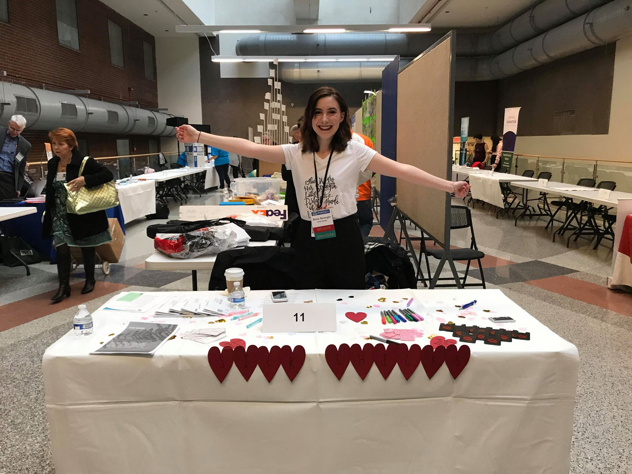 """[Image description: Shira is wearing a white printed T shirt with her arms extended smiling at the camera. She is standing behind a table covered in a white table cloth with """"SICK CHICKS"""" written in red cutout hearts at the front of the table.]"""
