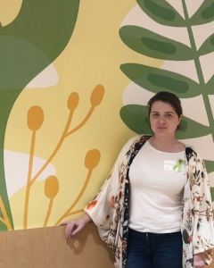 [Image description: Teri is standing in front of a painted wall of large green and yellow colored plants. Teri is wearing a white top with a name tag sticker and a floral printed sweater.]