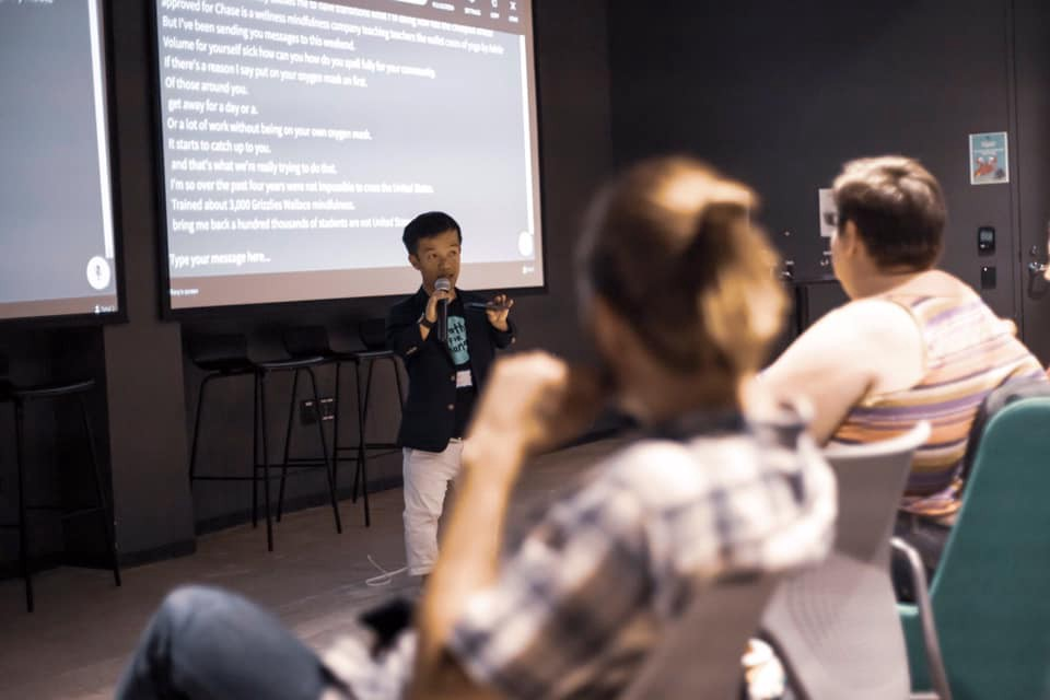 Danh Trang speaking into a microphone with captions in white on the screen behind him. Photo credit: Kai Faust