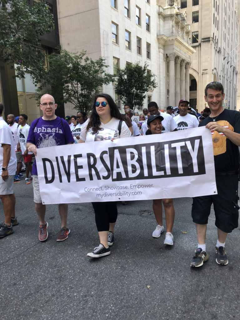 [Image Description: Four 2019 Disability Pride NYC parade goers holding a Diversability banner.]