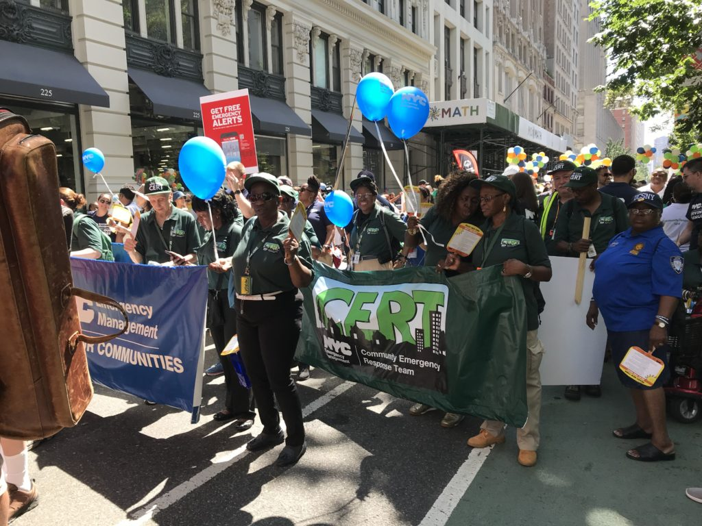 [Image Description: Multiple groups marching in the 2019 Disability Pride NYC Parade holding banners and blue balloons.]