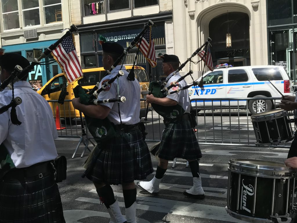 [Image Description: A group of bag pipers marches in the 2019 Disability Pride Parade.]
