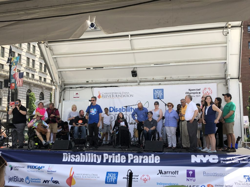 [Image Description: The 2019 Disability Pride NYC Parade main stage depicting event organizers and VIP's.]
