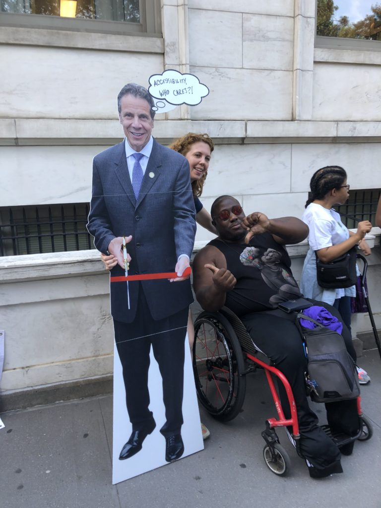 [Image Description: 2019 Disability Pride NYC Parade participants posing with a comical cutout image of Governor Cuomo.]