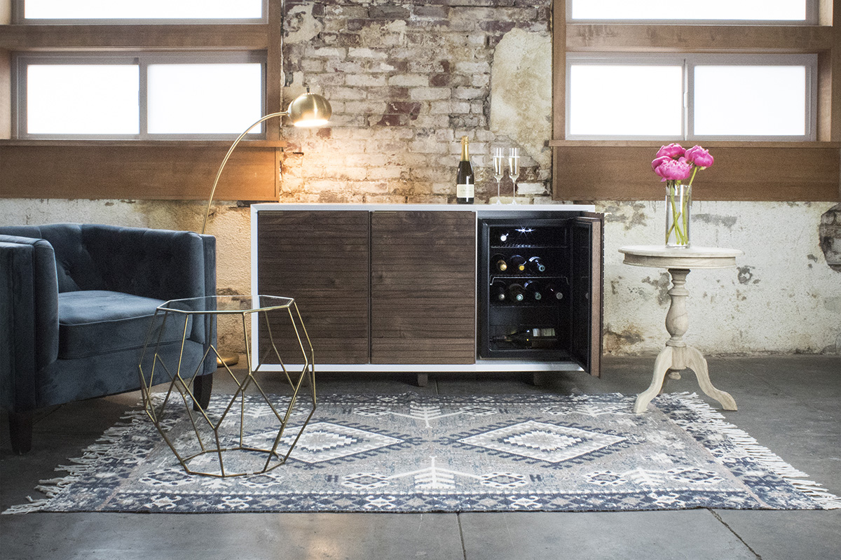 A beautifully crafted wine fridge, a favorite armchair and a classic rug are investments that can be restyled any number of ways with different side tables, lighting and accessories. ~  Photo by Sommi Wine Cellars