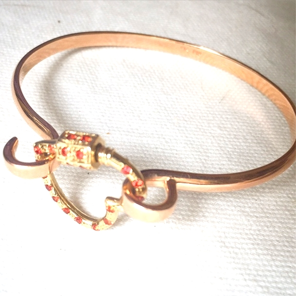 A custom, heart shaped 'Hard Lock' with orange sapphires.