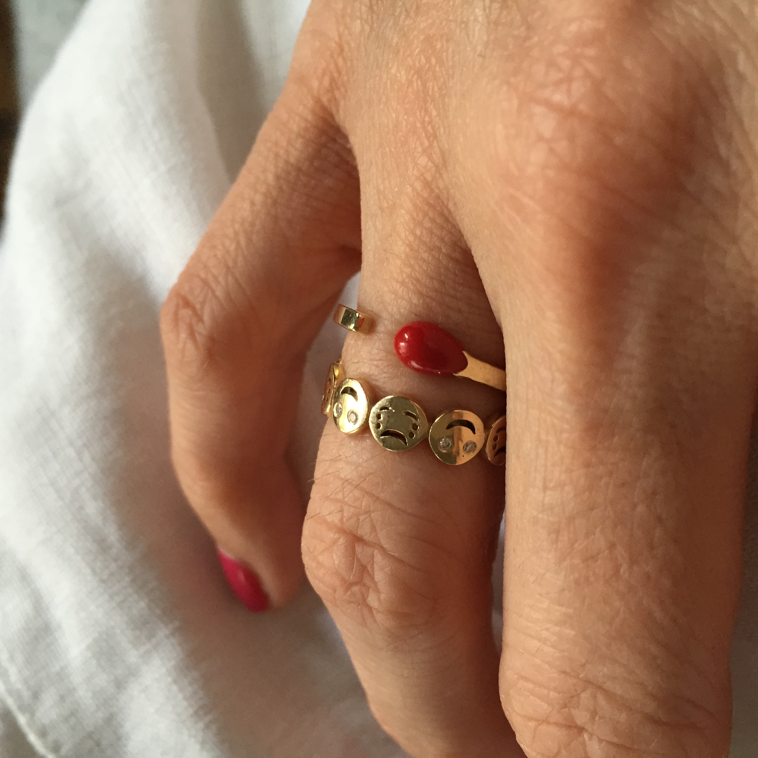 "Nadine wearing her  Alison Lou ""Happy or Sad?"" ring  with a  Nora Kogan Red Matchstick  ring, both available at Stone & Strand."