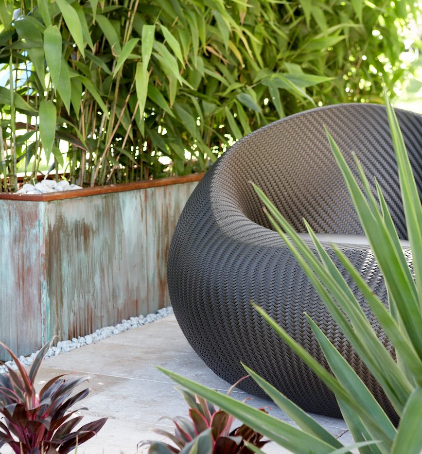 Tumbled travertine tiles and timber accents give the area softness -a copper planter box adds extra interest and texture, and contrasts well with the soft foliage. The woven loveseat is a prominent and practical feature that invites you to relax.