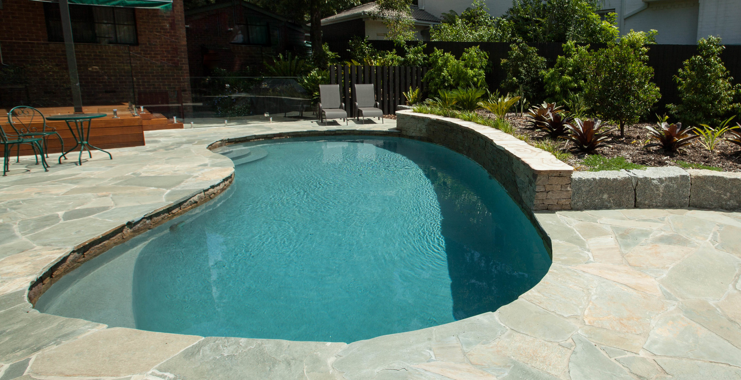 AFTER: A big improvement! Granite crazy paving gives a nod to the local area, as well as tying in well with the granite accents in the waterfall and in retaining walls around the garden areas. The new pool surface is light grey, making for a much more refreshing looking swim! Visibility from the new and improved decked entertaining area is much better, too, thanks to the frameless glass pool fencing. Timber posts give an extra detail, are pool safe, and break up all the fencing at each end.