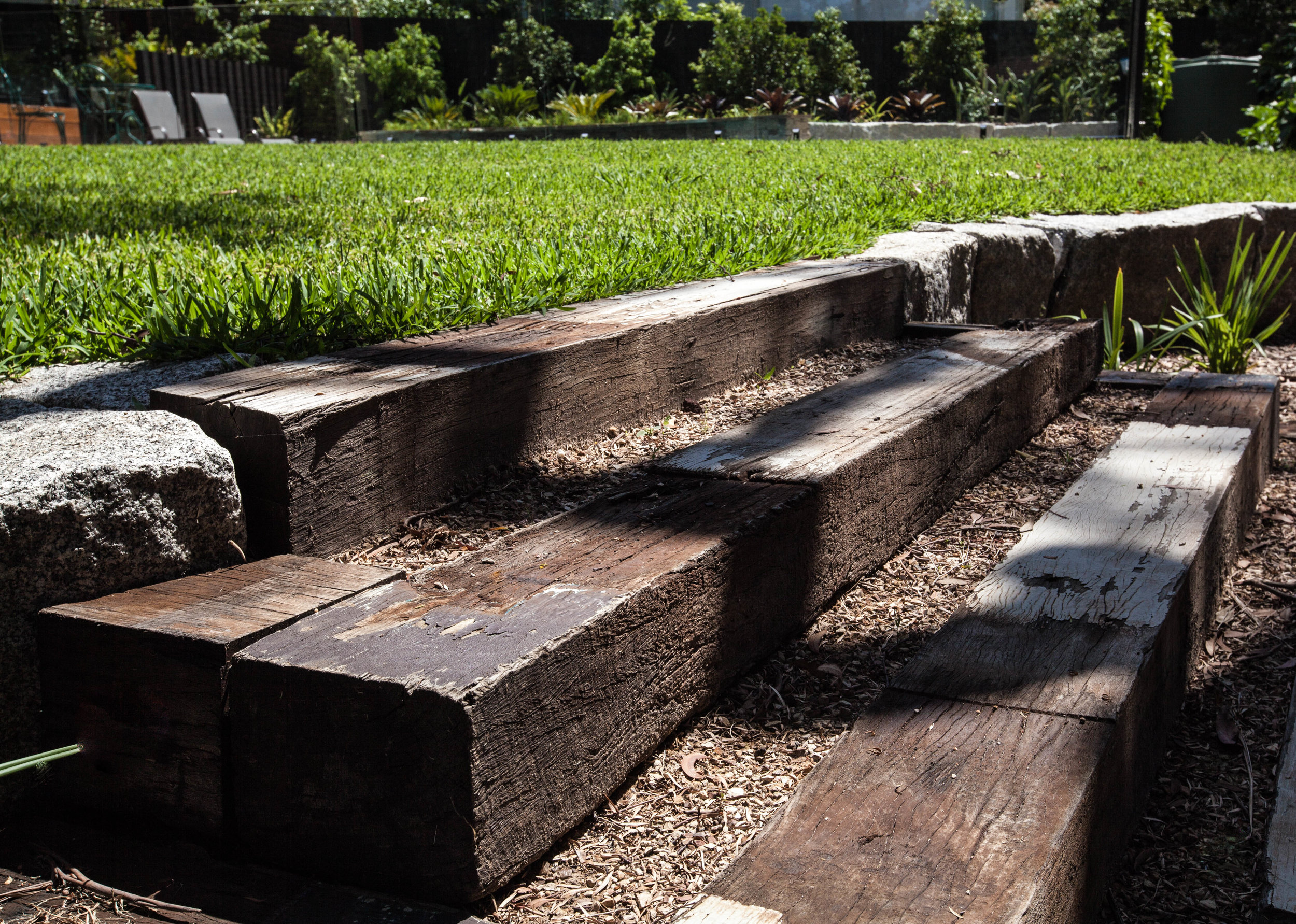 Recycled timber steps lead up from the sunken campfire lounge to the lawn area. Bolstered granite blocks serve as retaining walls to give the lawn a lift and to tie in with the granite in the pool area.