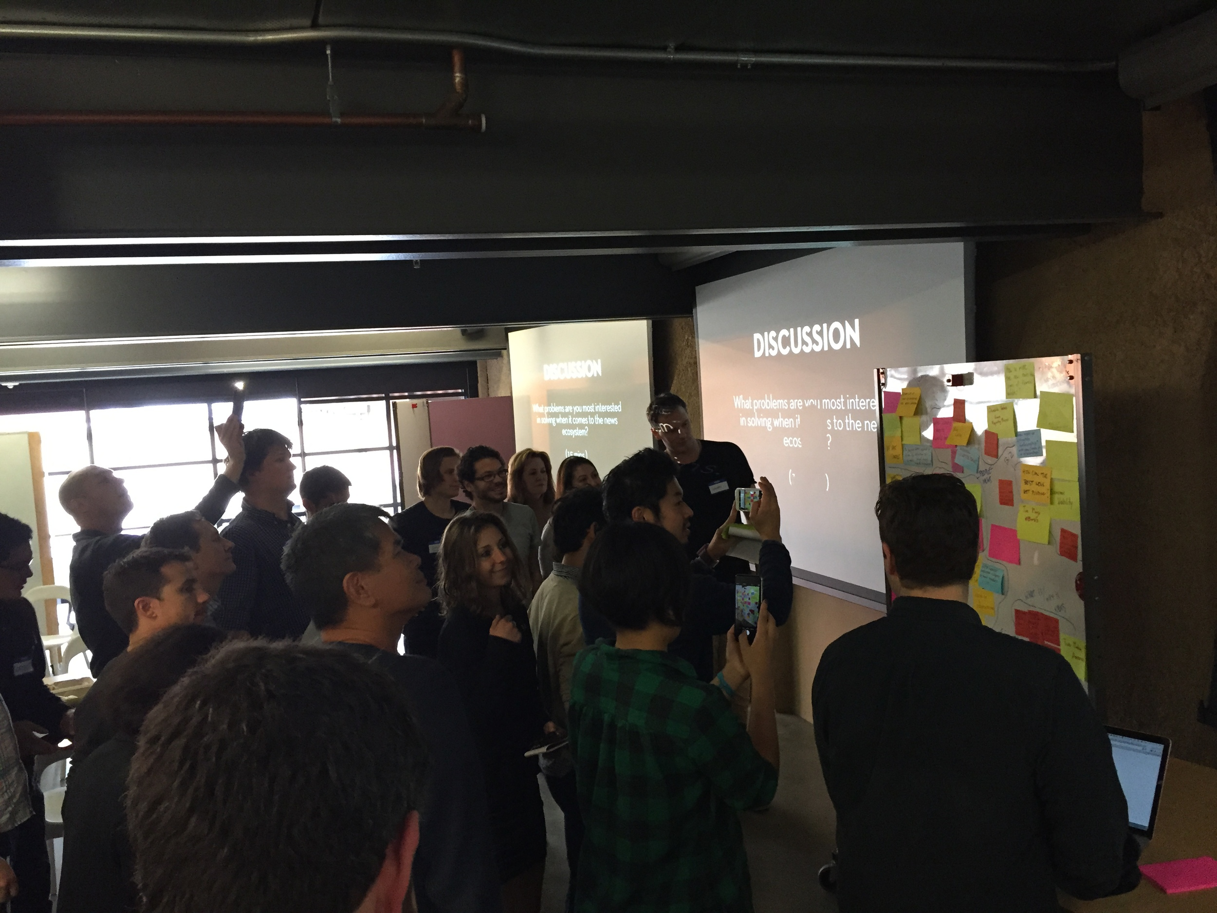 The class gathers around a whiteboard full of ideas ... lots and lots of ideas. (Emi Kolawole)
