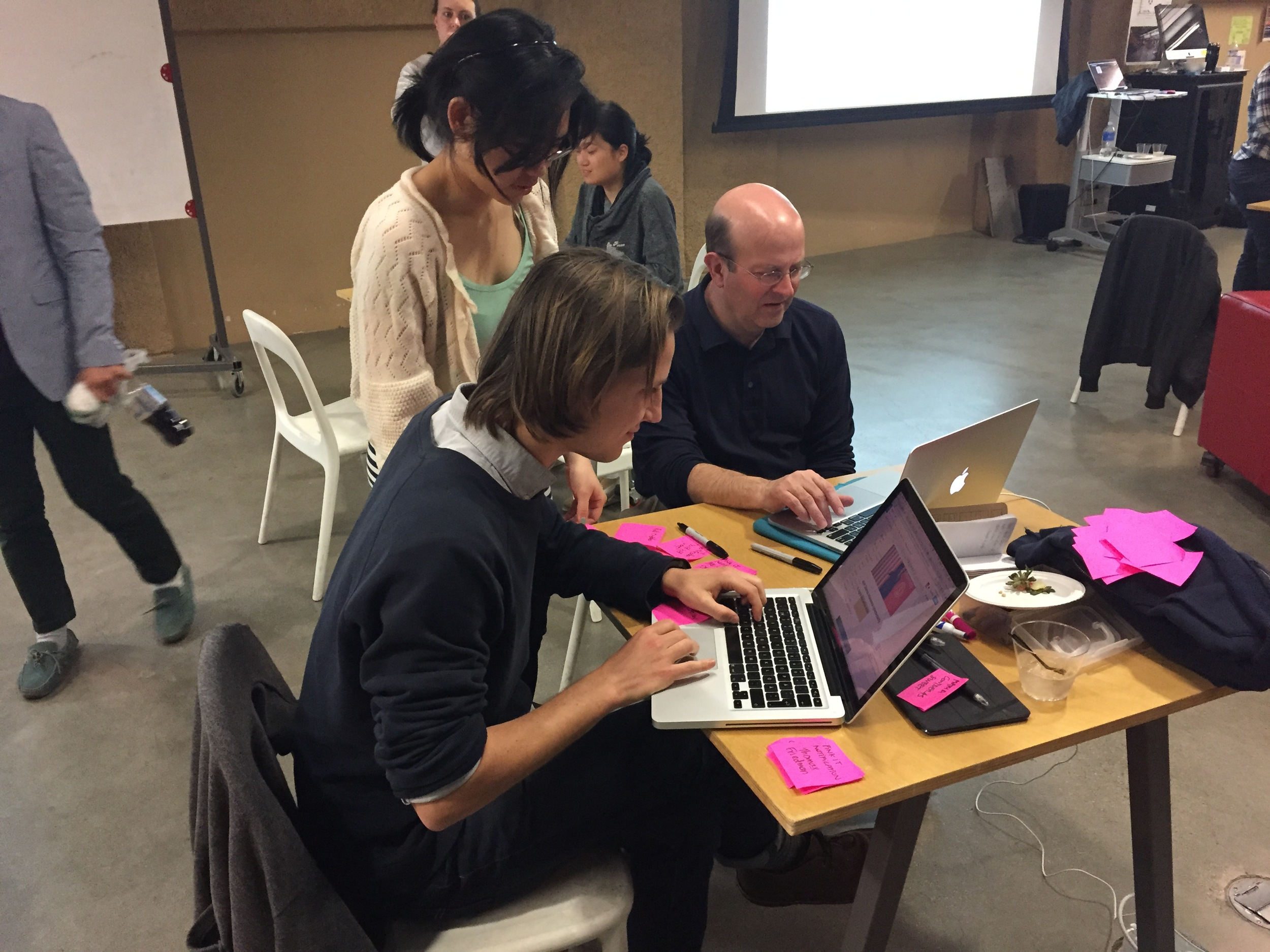 """Students work with Jay Hamilton, the Director of Stanford's Journalism Program, (right) testing """"Pink It"""", one of the prototypes created during class. (Emi Kolawole)"""