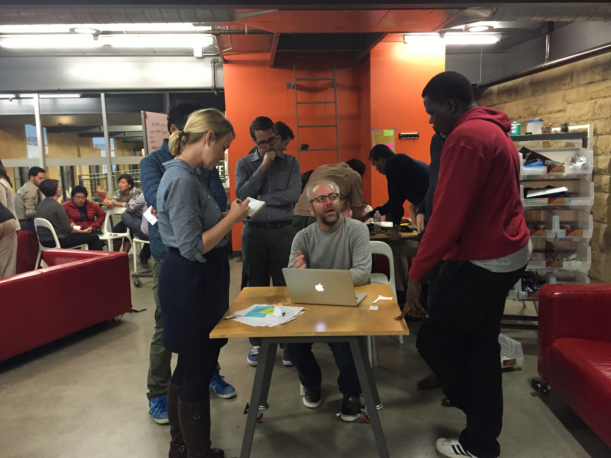 Mike Davidson, Vice President of Design at Twitter (center) works with students as they test their prototypes. (Emi Kolawole)