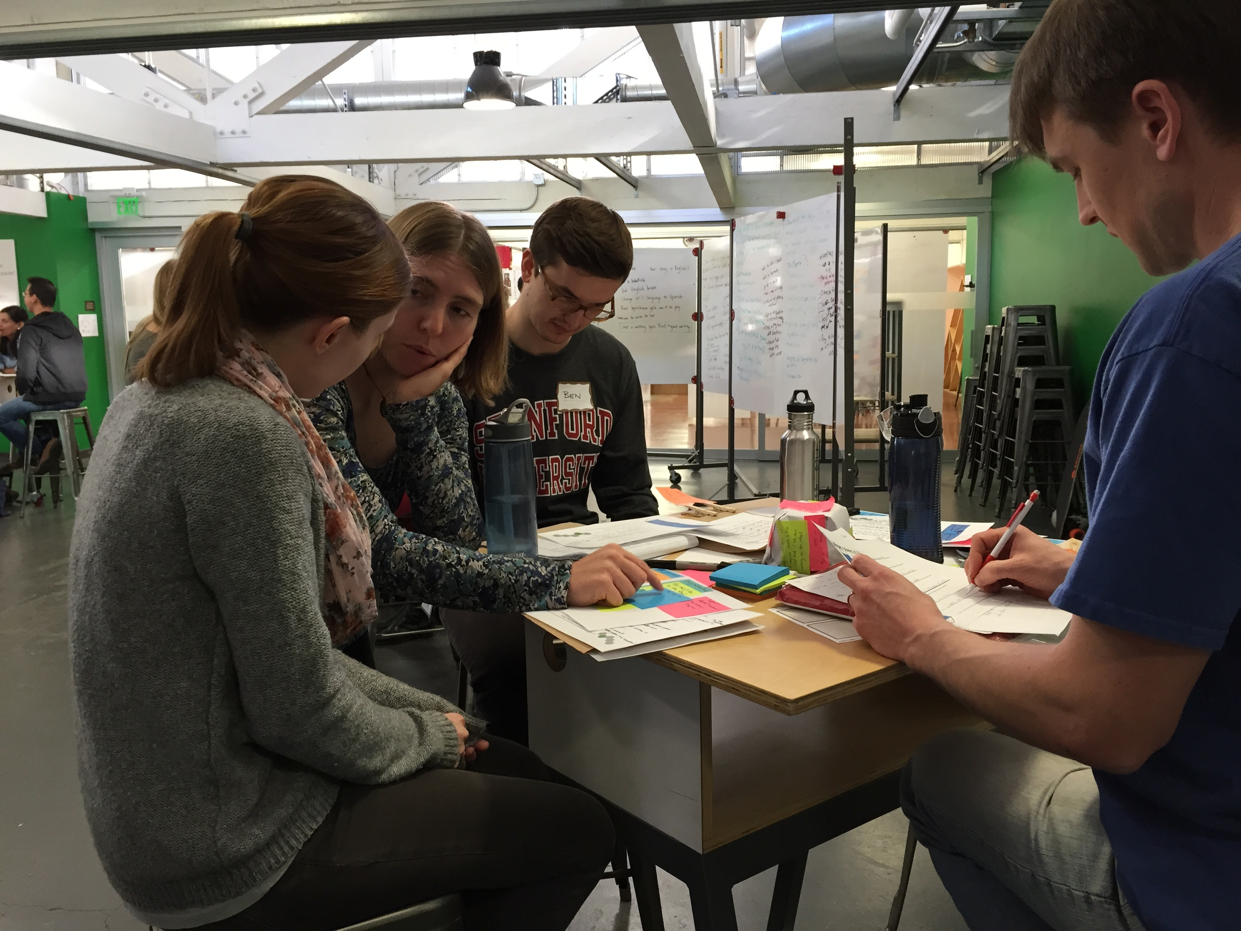 Amanda (middle ground) sits with students as they learn to apply design thinking to their work. (Emi Kolawole)