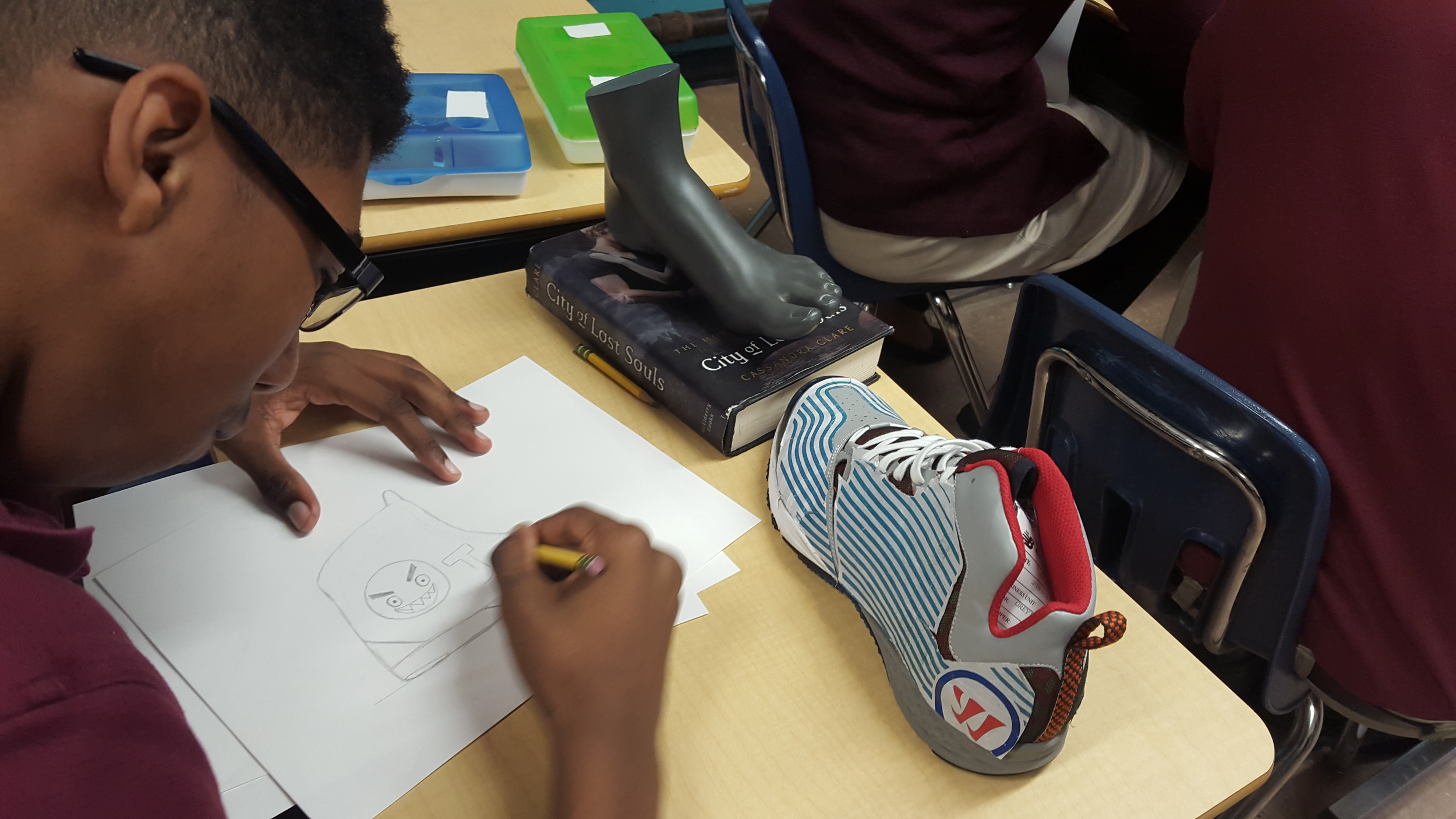Guest artist Sa'rah Melinda, a designer for the Adidas custom men's line, visited Boston Prep art classes to teach students about the application of art in the design profession. Here, Rodney Owens creates his own show design.