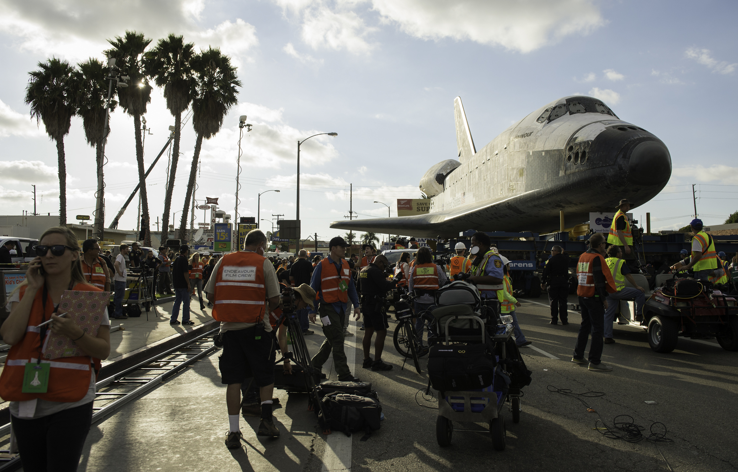 Support personnel and film crews are seen working around the space shuttle Endeavour as it traverses through Inglewood, Calif. on Friday, Oct. 12, 2012. Endeavour, built as a replacement for space shuttle Challenger, completed 25 missions, spent 299 days in orbit, and orbited Earth 4,671 times while traveling 122,883,151 miles. Beginning Oct. 30, the shuttle will be on display in the CSC's Samuel Oschin Space Shuttle Endeavour Display Pavilion, embarking on its new mission to commemorate past achievements in space and educate and inspire future generations of explorers. (NASA/Carla Cioffi)