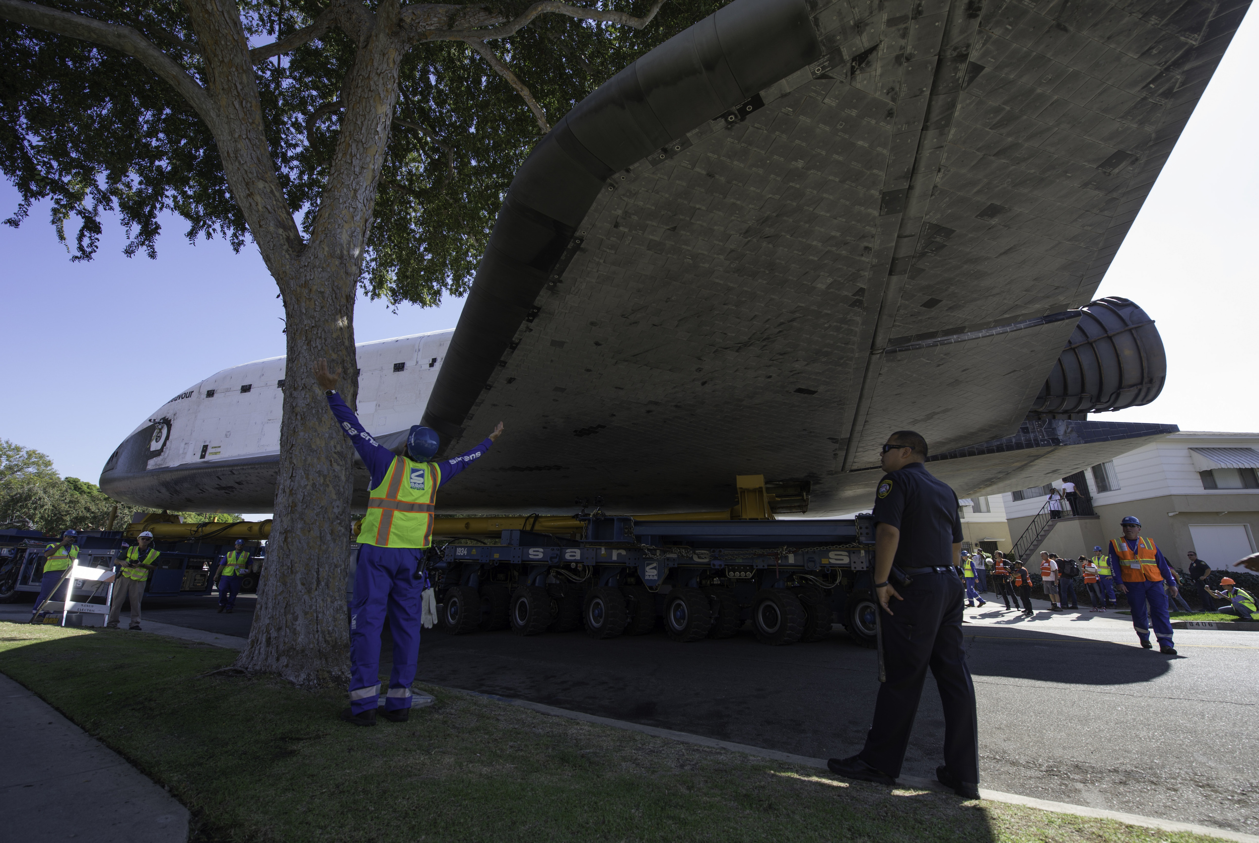 A technician for the Over Land Transporter (OLT) carrying the space shuttle Endeavour signals how much room is available between a tree and the orbiter's wing, Saturday, Oct. 13, 2012, as it maneuvers its way through the streets of Inglewood, Calif. Endeavour, built as a replacement for space shuttle Challenger, completed 25 missions, spent 299 days in orbit, and orbited Earth 4,671 times while traveling 122,883,151 miles. Beginning Oct. 30, the shuttle will be on display in the CSC's Samuel Oschin Space Shuttle Endeavour Display Pavilion, embarking on its new mission to commemorate past achievements in space and educate and inspire future generations of explorers. (NASA/Carla Cioffi)