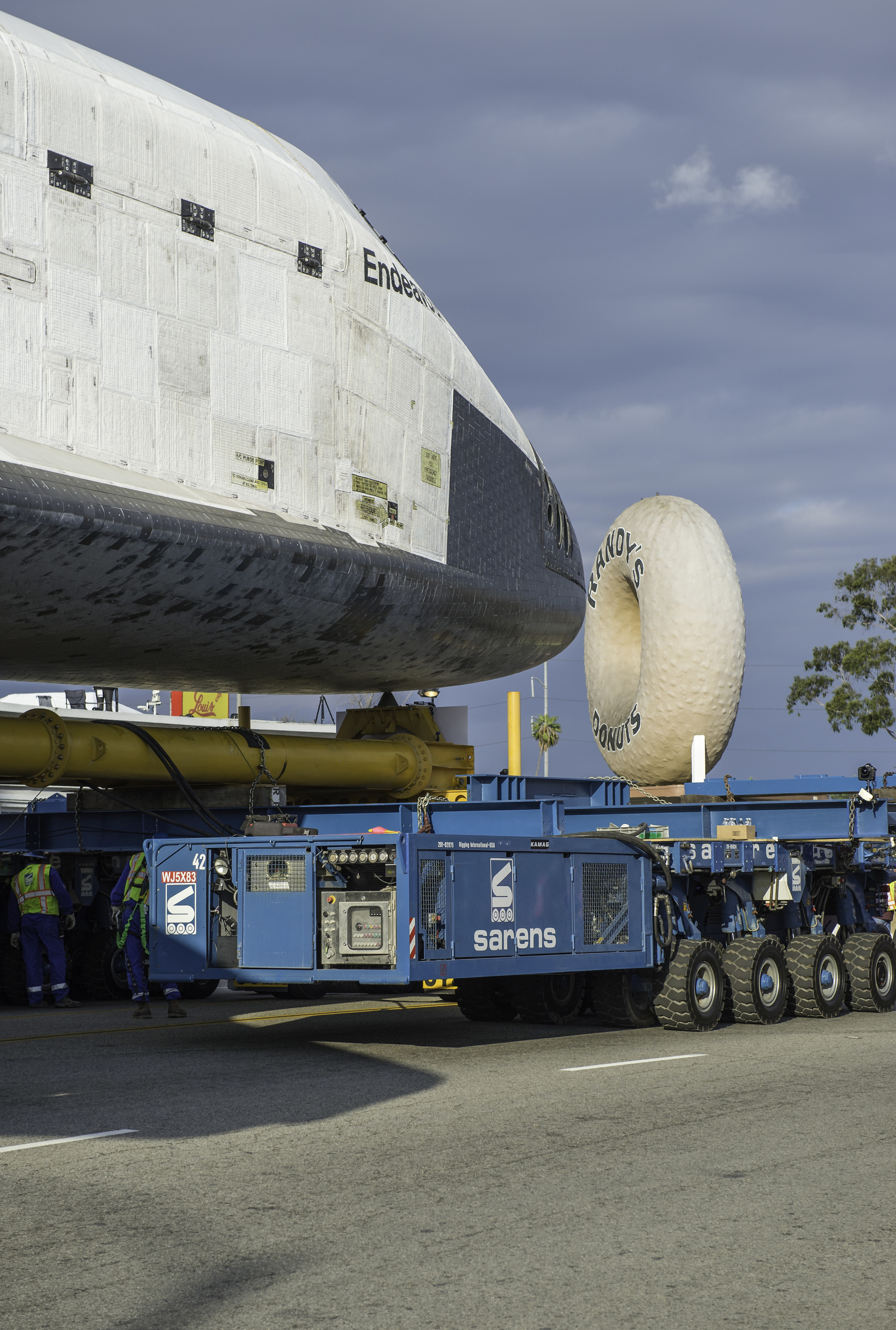 The nose cone of the space shuttle Endeavour is seen next to the Randy's Donuts landmark in Inglewood, California, Friday, Oct. 12, 2012. Endeavour, built as a replacement for space shuttle Challenger, completed 25 missions, spent 299 days in orbit, and orbited Earth 4,671 times while traveling 122,883,151 miles. Beginning Oct. 30, the shuttle will be on display in the CSC's Samuel Oschin Space Shuttle Endeavour Display Pavilion, embarking on its new mission to commemorate past achievements in space and educate and inspire future generations of explorers. (NASA/Carla Cioffi)