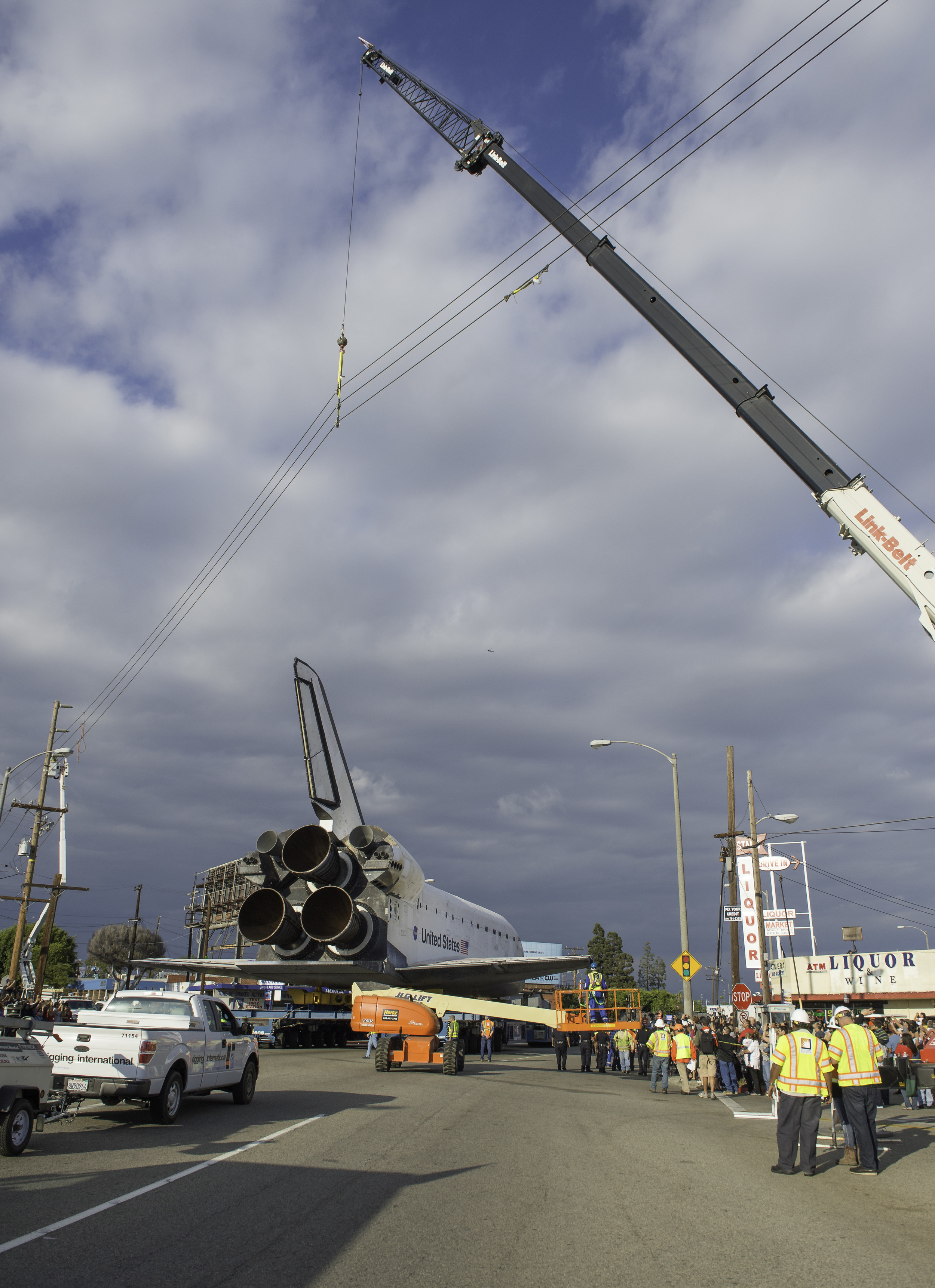 Power lines are hoisted upwards by a crane in order to allow the space shuttle Endeavour to traverse on its path to its new home at the California Science Center, Friday, Oct. 12, 2012 in Inglewood. Endeavour, built as a replacement for space shuttle Challenger, completed 25 missions, spent 299 days in orbit, and orbited Earth 4,671 times while traveling 122,883,151 miles. Beginning Oct. 30, the shuttle will be on display in the CSC's Samuel Oschin Space Shuttle Endeavour Display Pavilion, embarking on its new mission to commemorate past achievements in space and educate and inspire future generations of explorers. (NASA/Carla Cioffi)