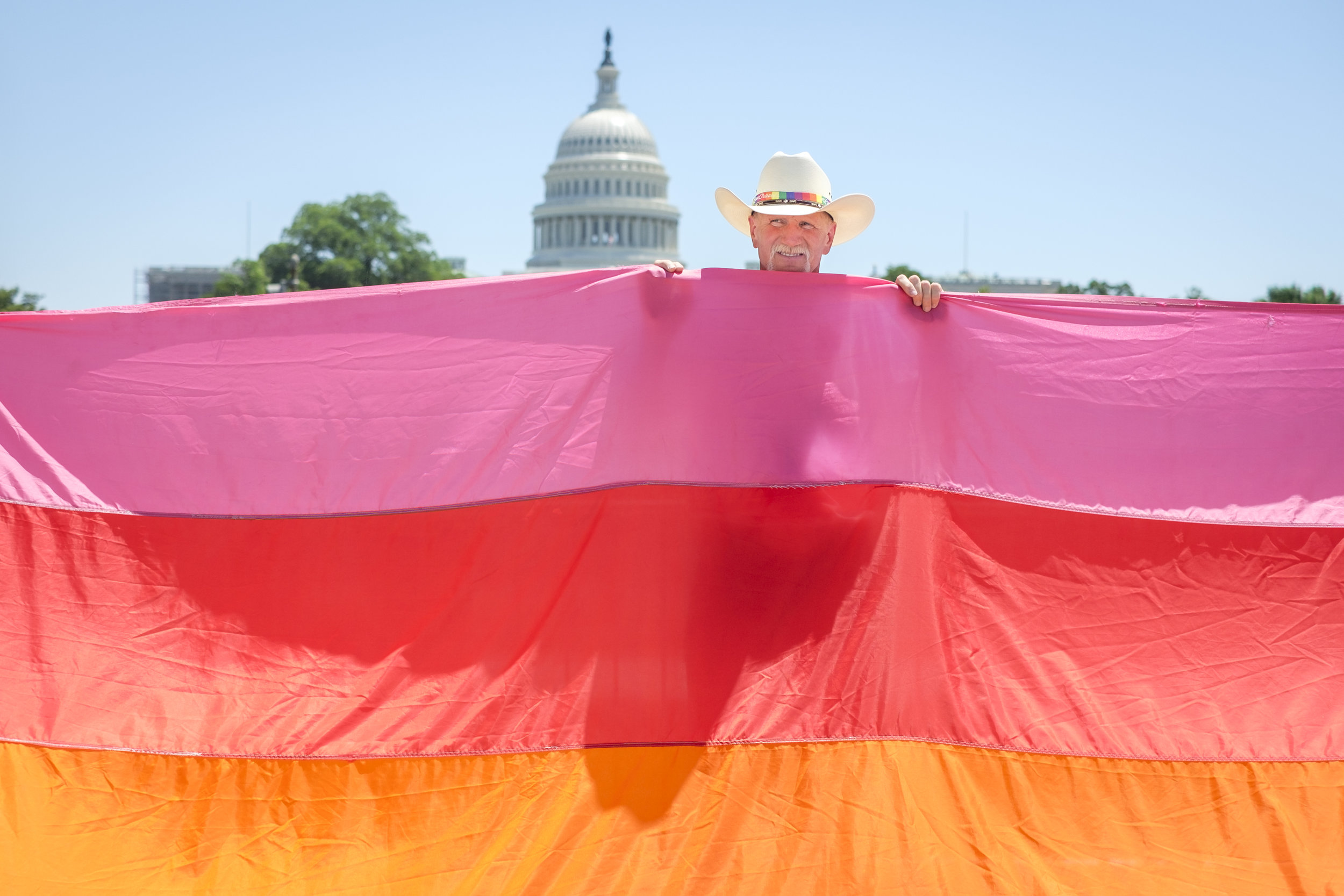 """Wes Givens of Plumerville, AR is seen holding up part of a large Rainbow Flag at the rally following the Equality March for Unity and Pride on Sunday, June 11, 2017 in Washington, DC. After the flag was folded Wes walked up to me and shared the following, """"I was a plaintiff from Arkansas. I was on the the Supreme Court steps the day of the hearing. And on the steps the day of the ruling."""" He is referring to the Supreme Court ruling of Obergefell v. Hodges on marriage equality. When asked why he was there at the march and rally he said, """"Because equality. I was actually the first plaintiff to get a divorce. And so I'm talking for don't stay in an abusive marriage. If you have trouble, even though you're gay, you can start over. I'm 55 and my husband ran off with a man 15 years younger, and I thought my world was over. And I turned it around!"""" Wes also shared that he's a certified cowboy. The Equality March for Unity & Pride is a grassroots movement which seeks to mobilize the diverse LGBTQ+ communities to peacefully and clearly address concerns about the current political landscapes and how it is contributing to the persecution and discrimination of LGBTQ+ individuals."""