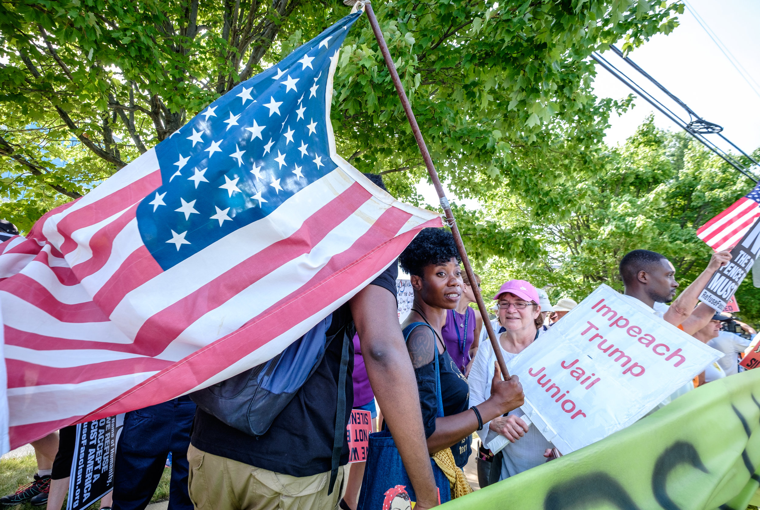 """Tamara Lee, from NYC, is seen at the Women's March From #NRA2DOJ rally at the National Rifle Association Headquarters in Fairfax, VA on Friday, July 14, 2017. """"I am … doing a research project on The Gathering for Justice, which is the umbrella organization that houses the Women's March, also the Justice League New York. And I think the important thing is that we have to protect the First Amendment rights to be out here, so when we have a propaganda that labels us as not peaceful. This is a tactic that we've seen before and we do the same thing we did then, which is to stand peacefully and say who we are. Right? So we're doing that. Also there is a problem in the country with the Second Amendment not being applied equally to black and brown folks. And we would like the NRA, if they are the organization that they say they are, to actually stand up for the rights of lawfully owning gun owners who are black and brown. So this is also about Philando Castile, which brings us to a larger issue. These are the intersectional issues that we're looking at where race and equality and women's rights, they're all tied together. … And so if we can't stand and resist this government peacefully then we don't have first amendment rights. If we don't have first amendment rights, you don't have second amendment rights. And if we don't have fourteenth amendment rights what are we here for? So that's why I'm here.""""  The Women's March from #NRA2DOJ is a demonstration against the NRA taking no action in response to the Philando Castile trial verdict. Following the rally demonstrators marched 18 miles from the NRA to the Department of Justice in Washington, DC."""