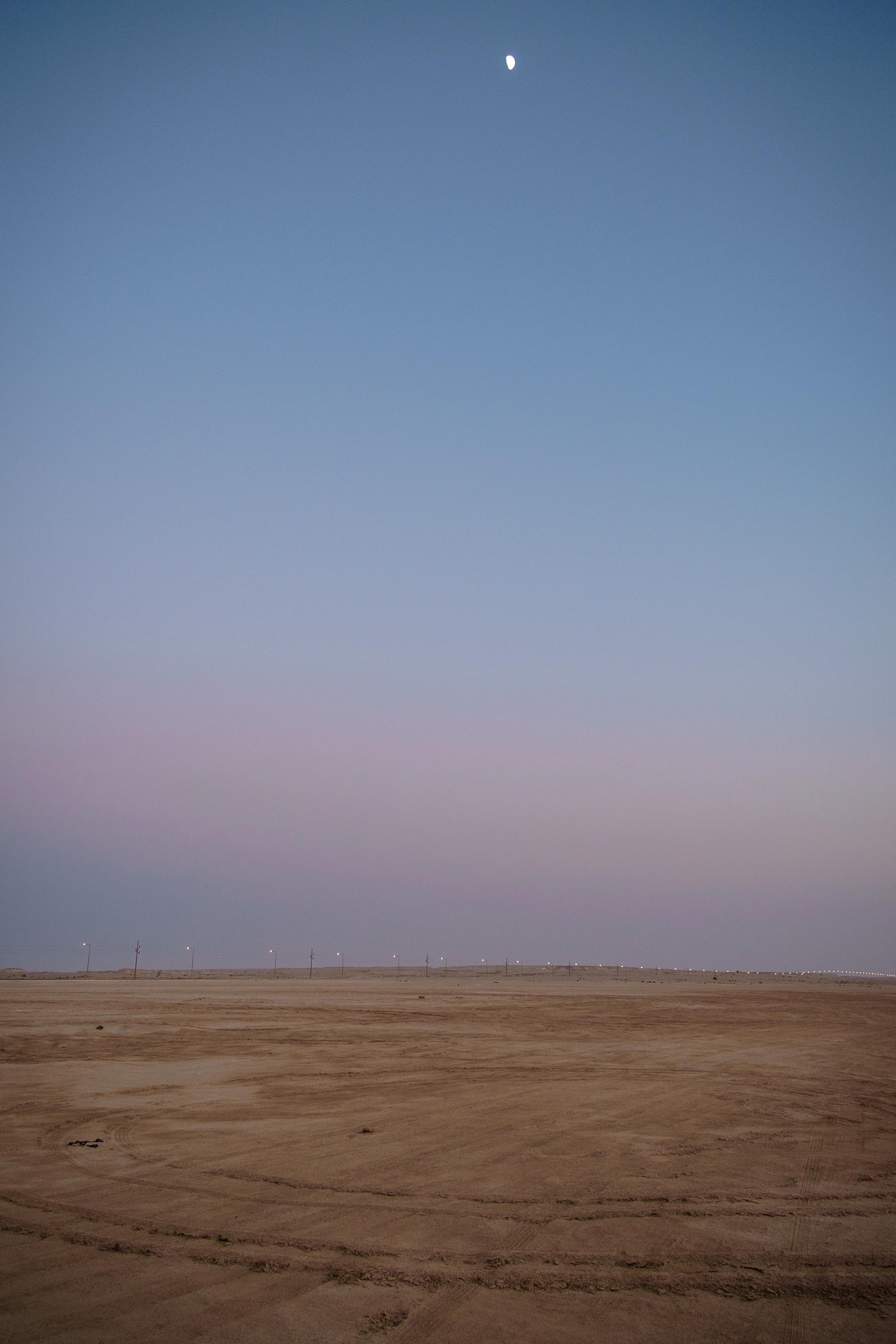 The moon is seen rising above the desert in Zekreet at dusk.