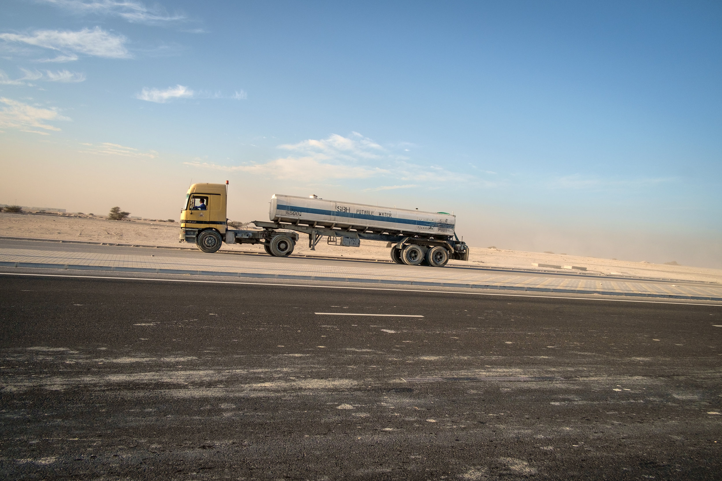 The ubiquitous semi truck, this one carrying water, is seen at sunset leaving massive construction site on the outskirts of Doha.