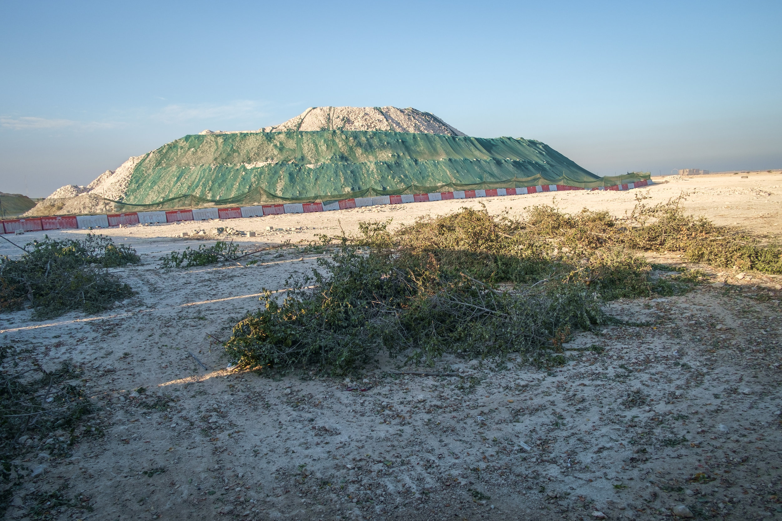 A massive mound of dirt and rock, echoing a half-built pyramid, is seen at a construction site just north of Doha.