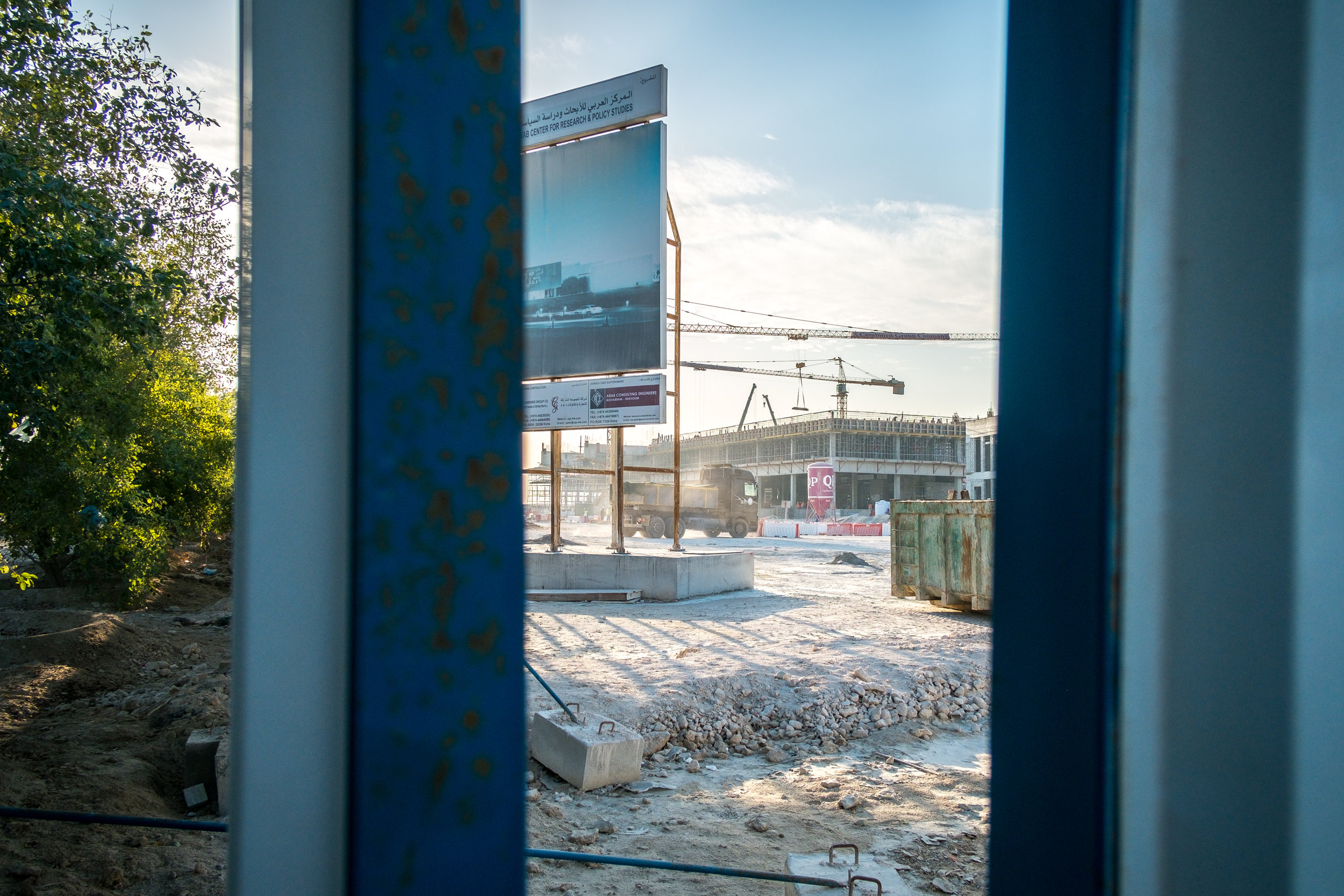 A construction site for the Arab Center for Research and Policy Studies is seen through a crack in the partition.