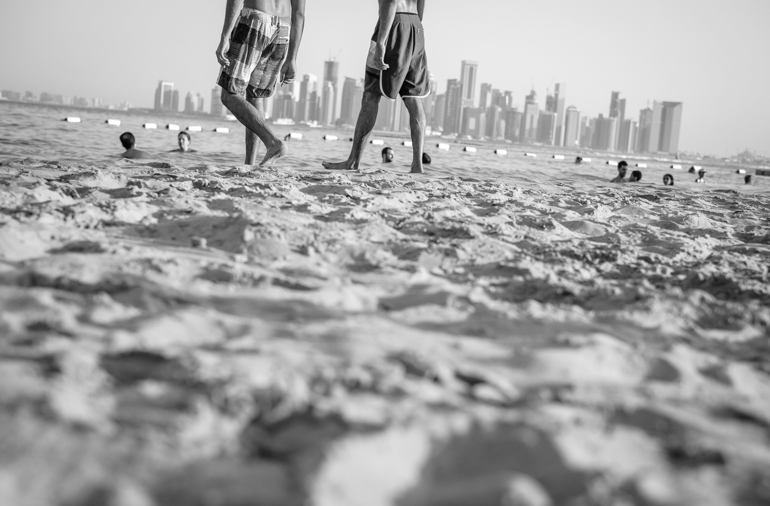 Expats enjoying the sun and sand at Nikki Beach on The Pearl in Doha. The Pearl is an artificial island comprising of luxury residential estates and businesses. It is the first land in Qatar made available for ownership by foreign nationals. The West Bay skyline is seen across the bay.