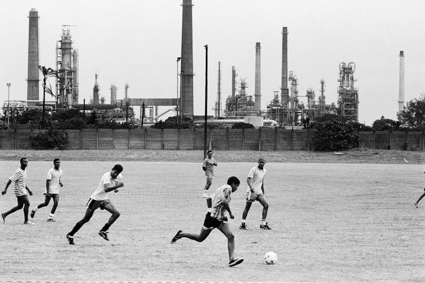 Soccer match on a sports field next to the SAPREF oil refinery, Wentworth, Durban, 1995