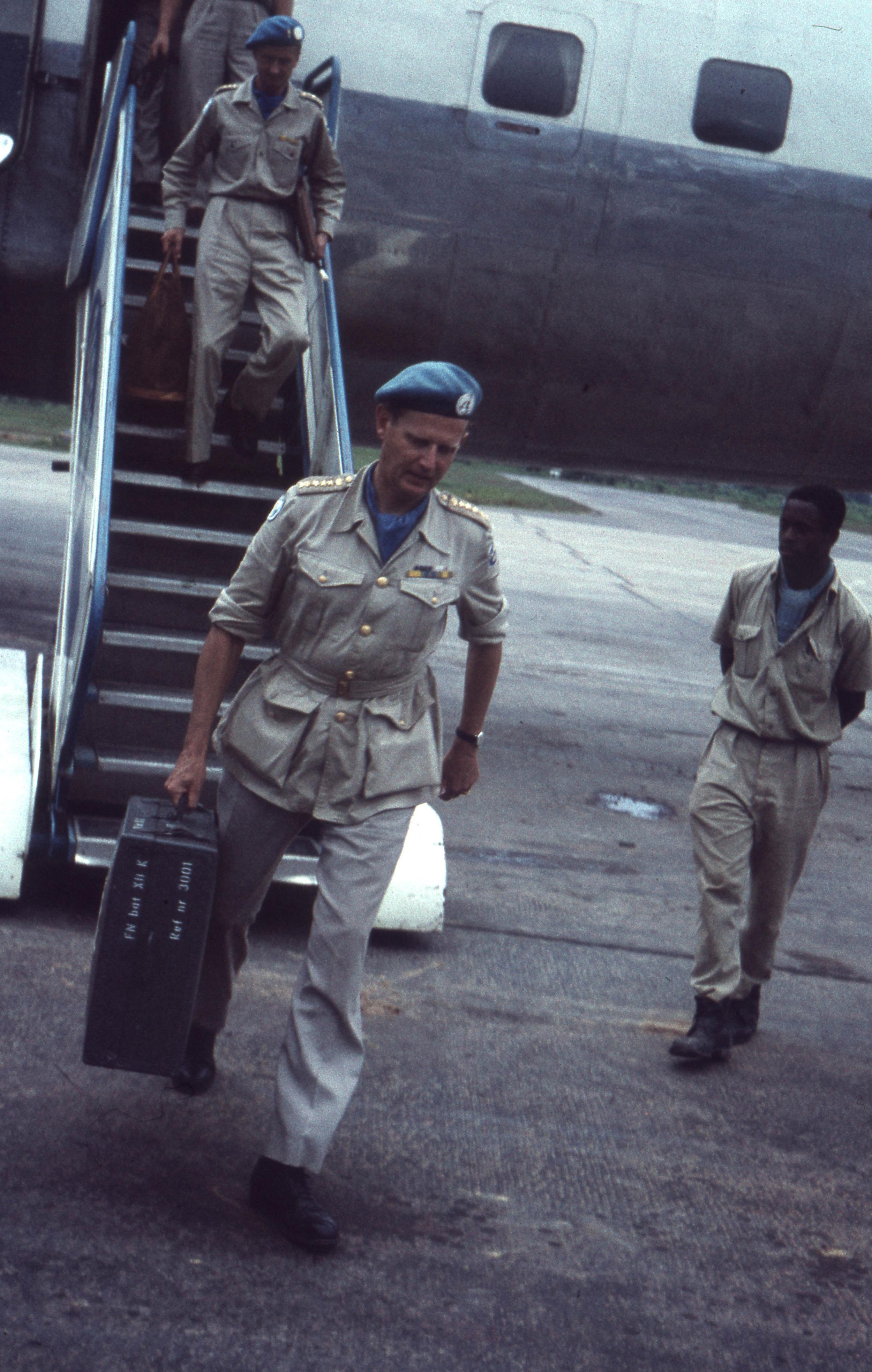 """Överste Jonas Waern stiger av flygplanet för att påbörja tjänstgöringen som chef för bataljon XIV (1961-1962) i Kongo. På väskan i hans högra hand kan man läsa """"FN bat XII K"""" - detta var Waerns andra vända till Kongo, och mycket skulle komma att hända under bataljon XIV. Vi kan bara gissa vilka tankar som far igenom hans huvud när han går över asfalten på flygplatsen. Foto ur Ernst Dahls arkiv. Ernst tjänstgjorde i Gaza (4G) samt i Kongo (XIV K)."""