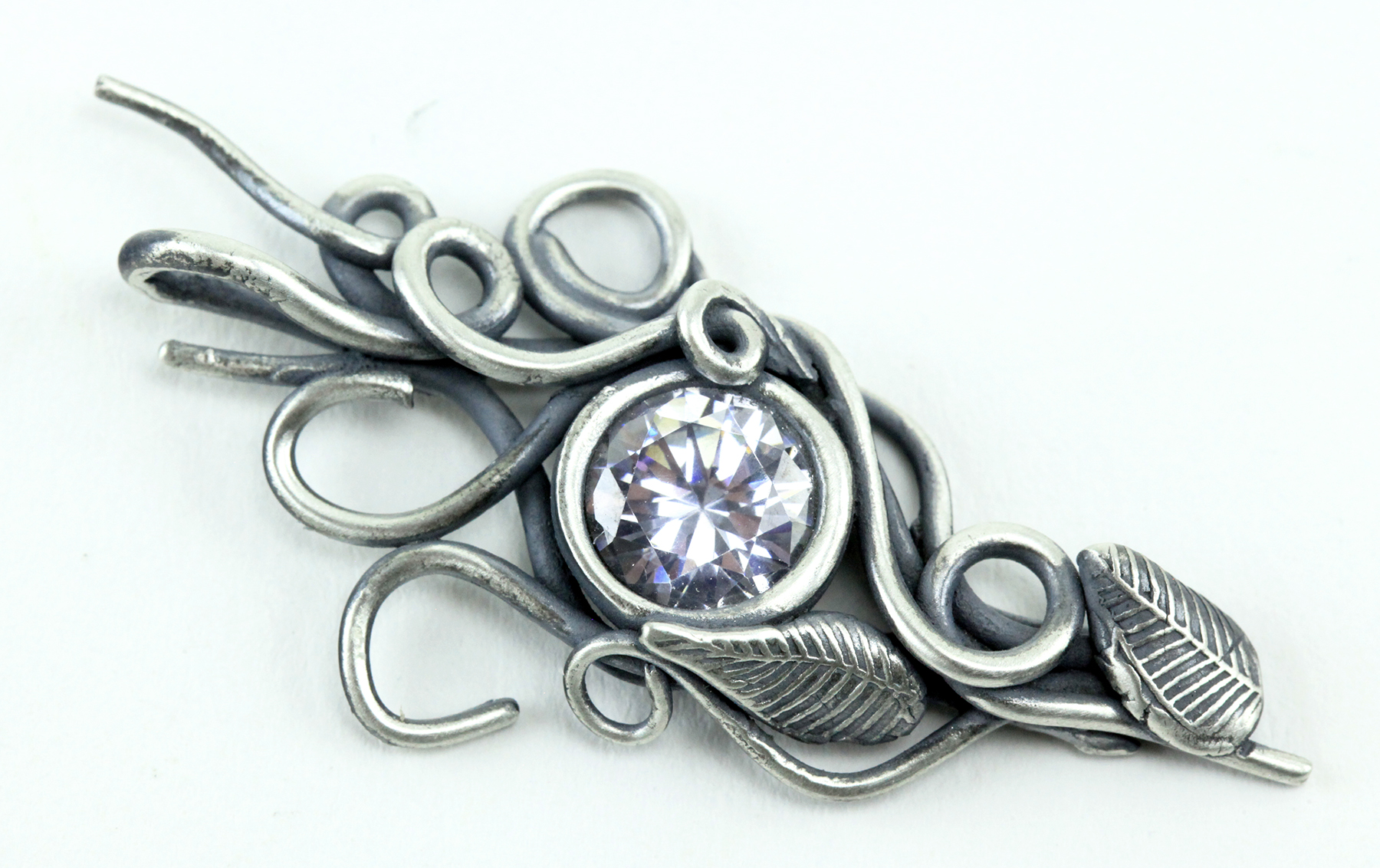 Bezel set cubic zirconia, combined with delicate coils and textured leaves