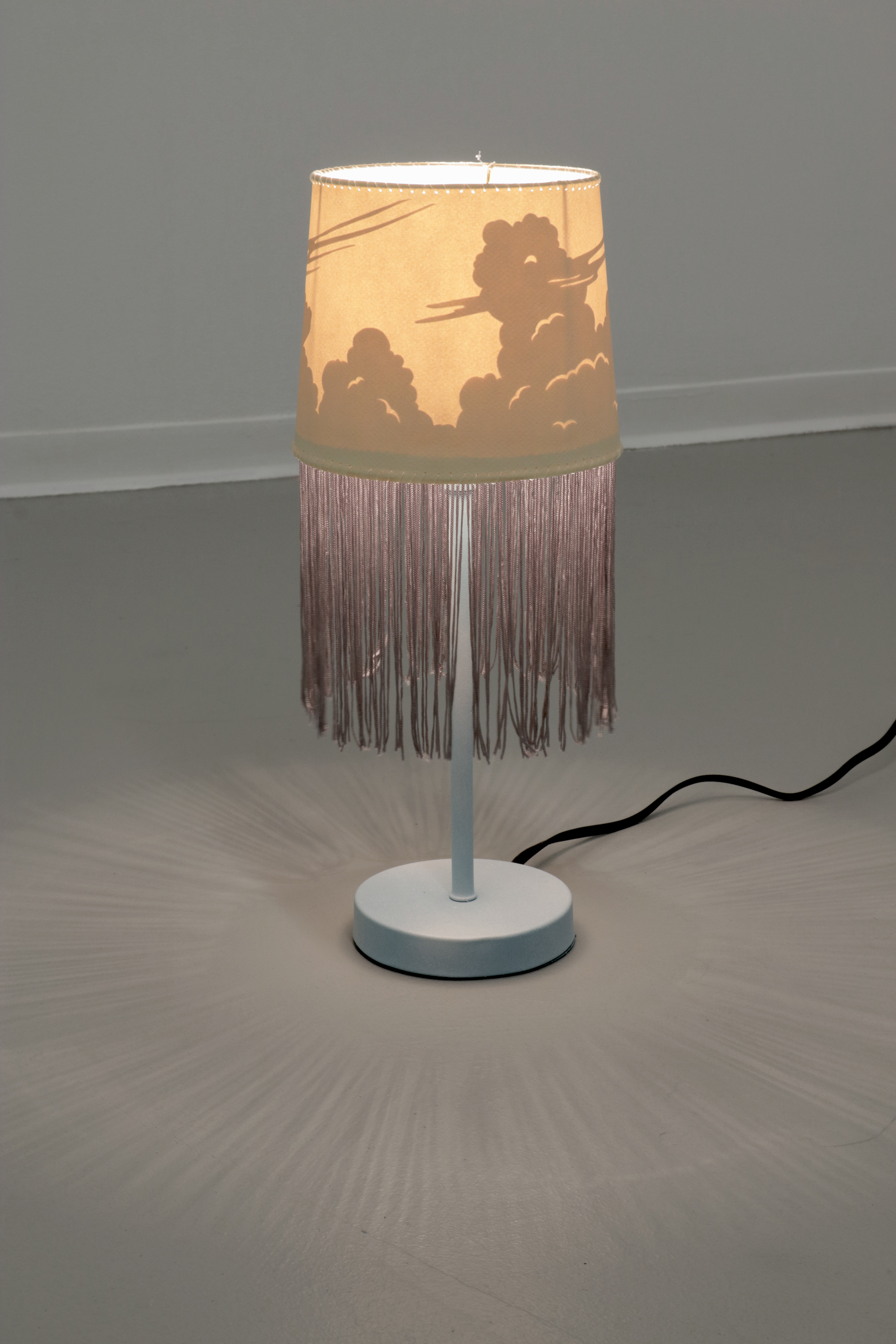 Untitled 2017 Motion-inactivated lamp, paper, fringe, fishing line, spraypaint