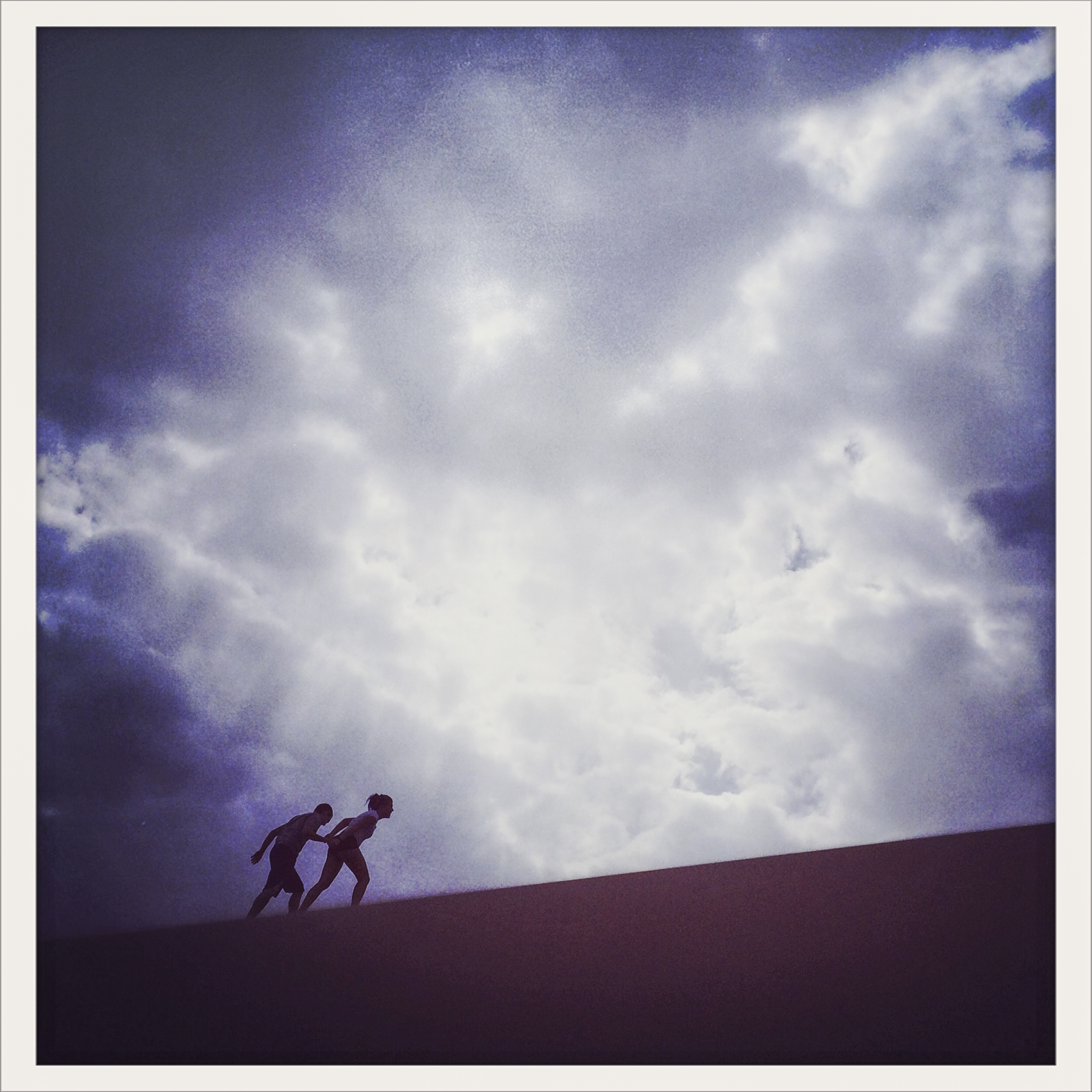 A couple help each other climb a large dune at the Great Sand Dunes National Park in Mosca, Colorado on Monday May 26, 2014.