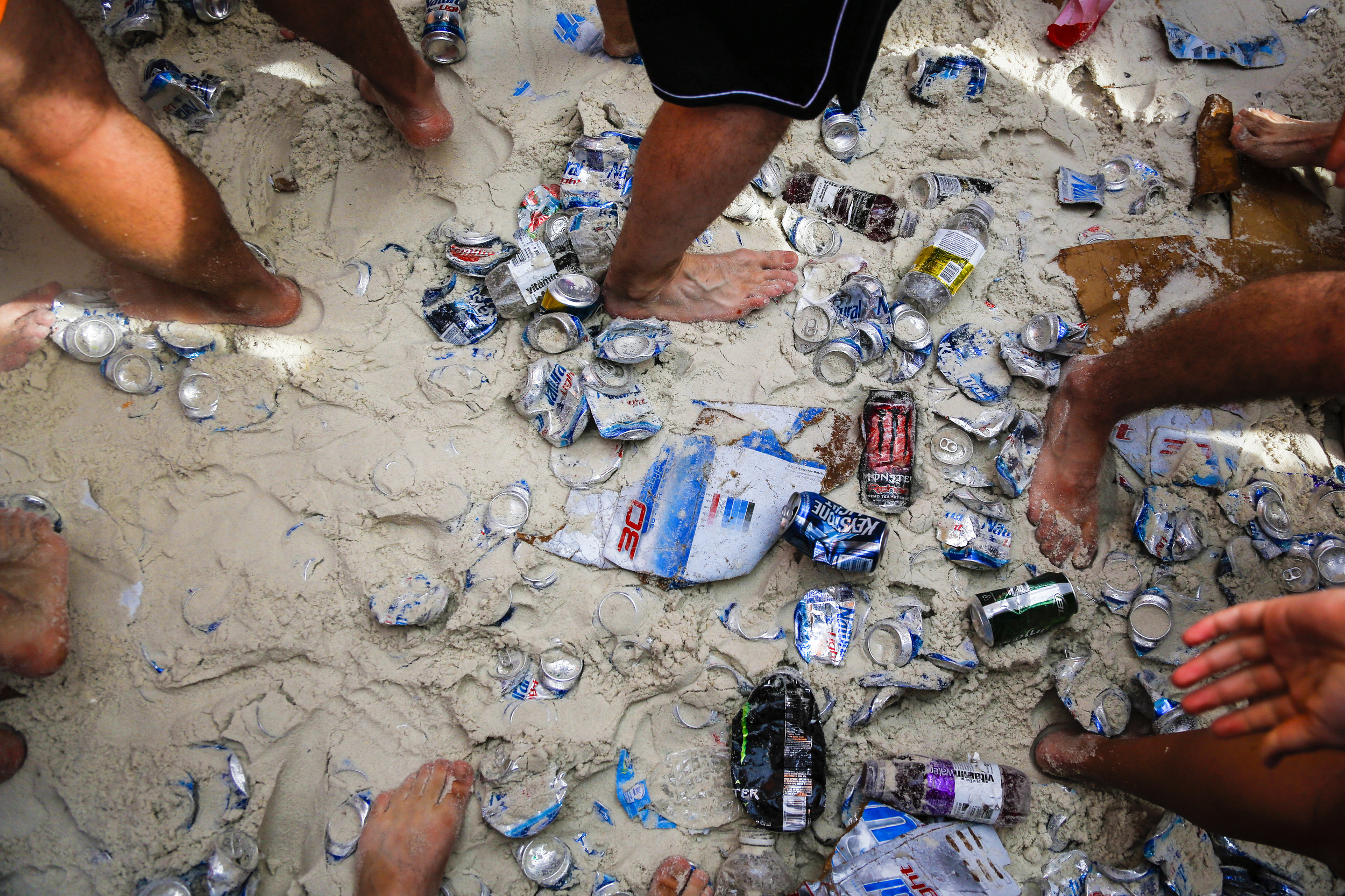 Spring breakers walk and dance on various beverage cans that have been left on the beach as students from around the country congregate to party and have a good time in Panama City Beach, Florida.