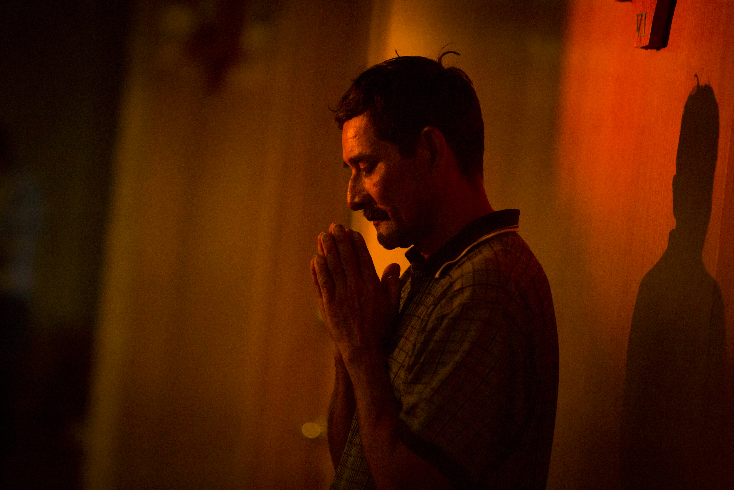 Antonio Mendez prays to the relic of Saint Toribio Romoas, the Catholic saint of immigrants and border crossers, from the back of the room at Santiago de Compostela Church in Lake Forest on Friday July 11, 2014.