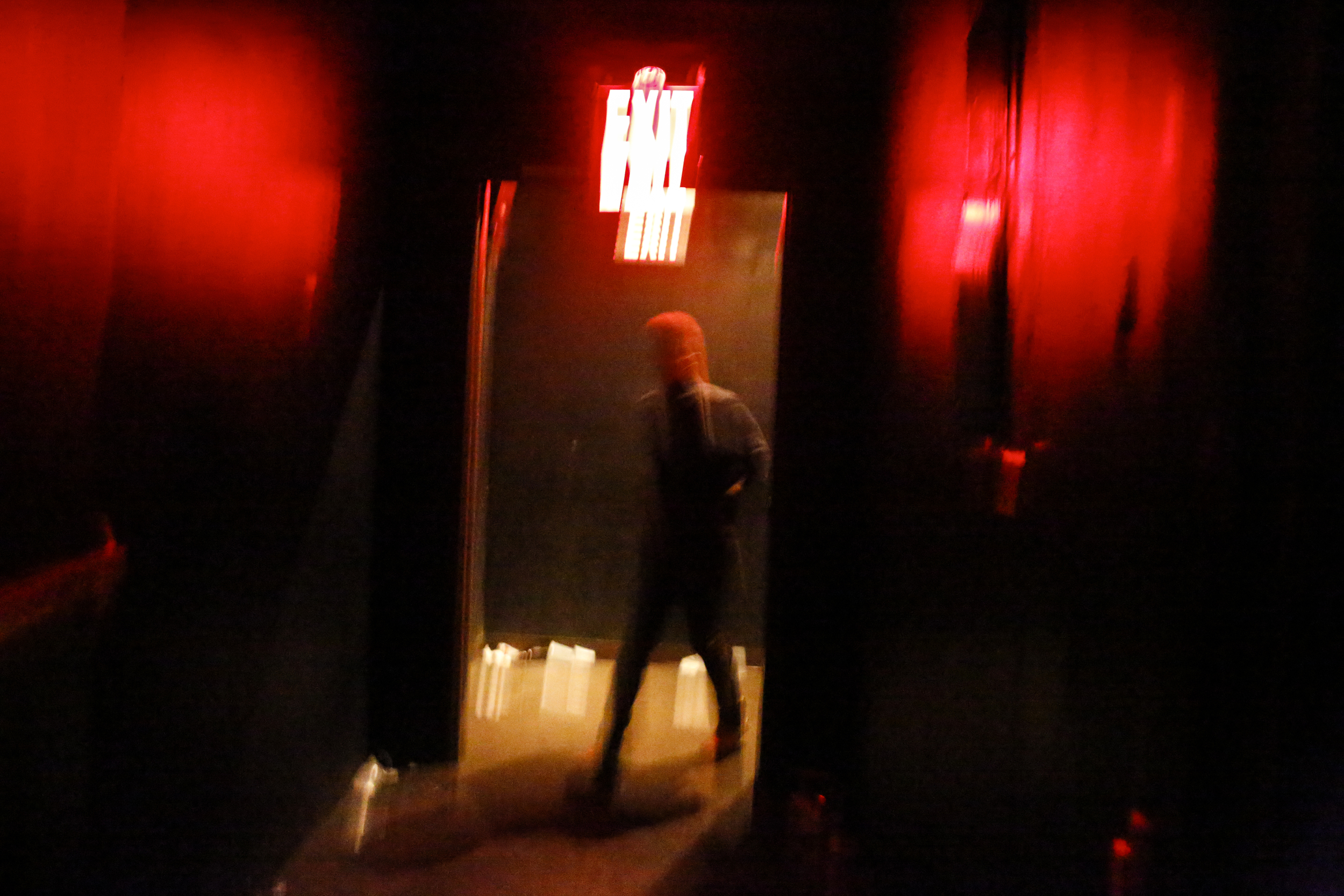 A women walks into one of two dance rooms at a club on new years in Brooklyn, New York.