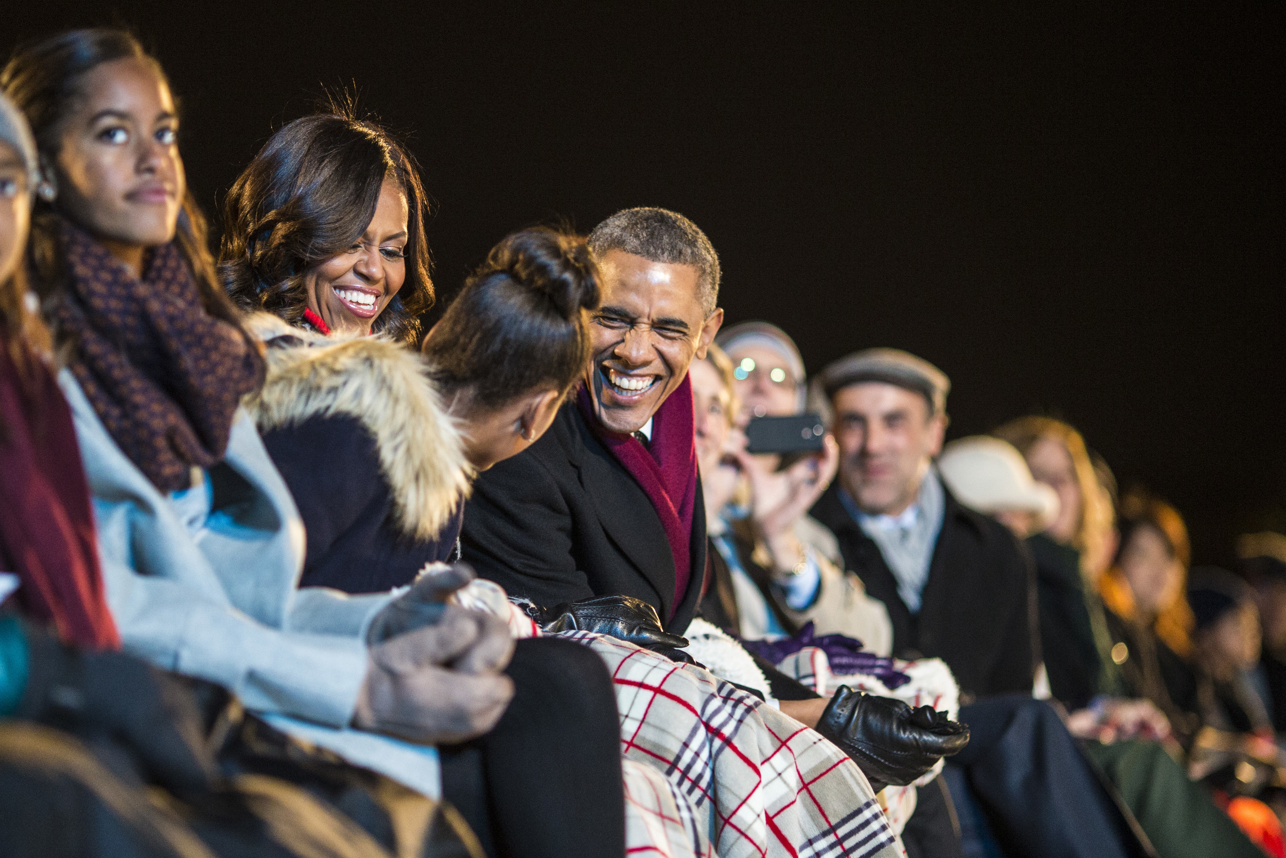 President Barack Obama, first lady Michelle Obama, and their daughters Sasha, second from left, and Malia, left, listen to performances during the National Christmas Tree Lighting ceremony at the Ellipse in Washington, DC on Thursday December 04, 2014.