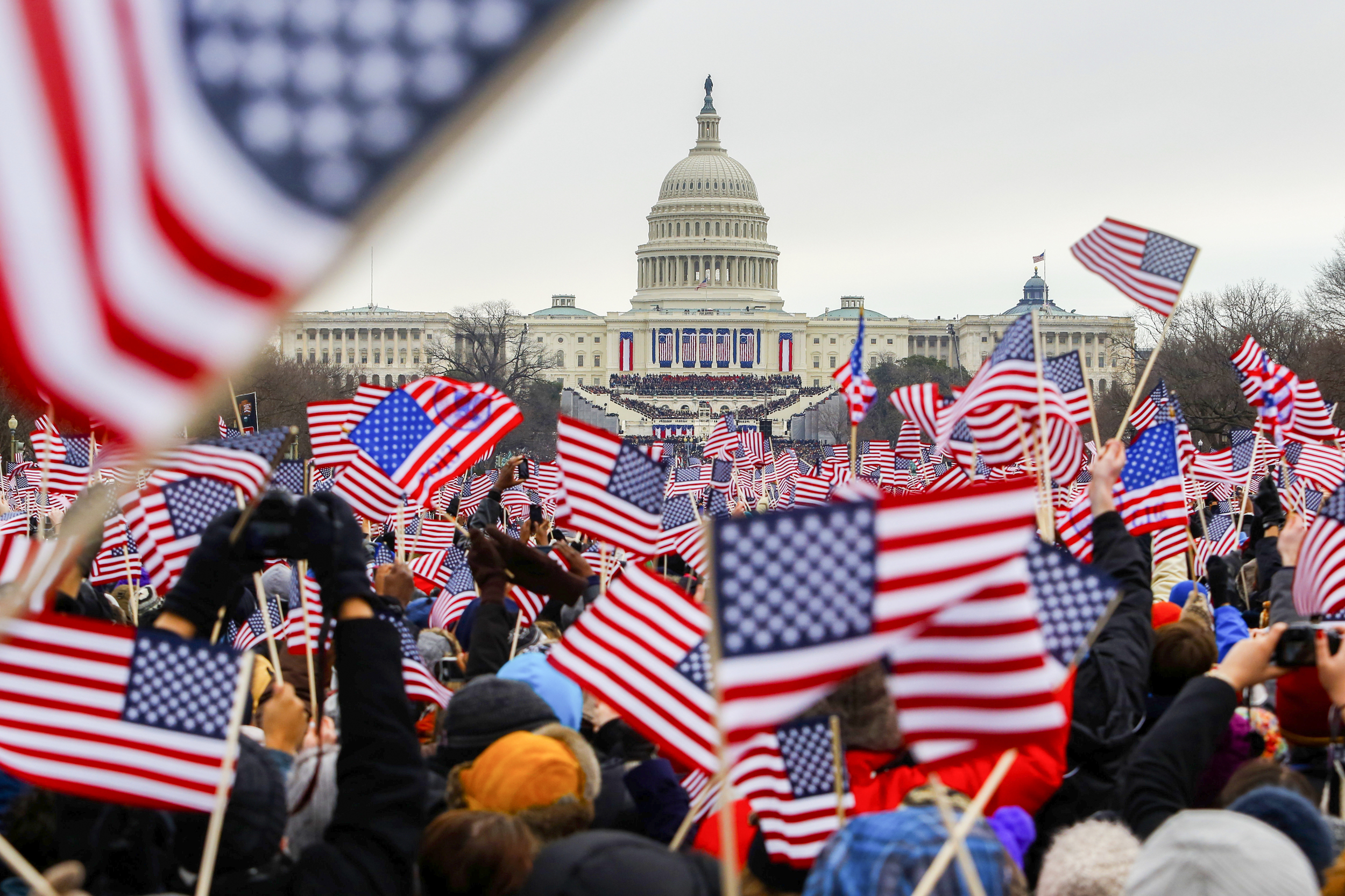 Patrons wave flags at the National Mall as President Barack Obama was introduced at his ceremonial swearing-in at the U.S. Capitol during the 57th Presidential Inauguration in Washington, Jan. 21, 2013.