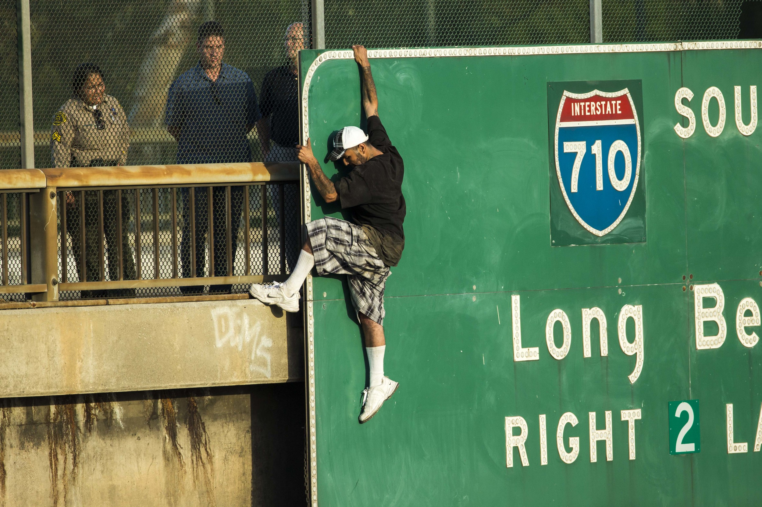 A man thought to be trying to jump climbs on a freeway sign on the Downey Rd. bridge over the 5 causing both directions to be closed on Friday July 25, 2014.