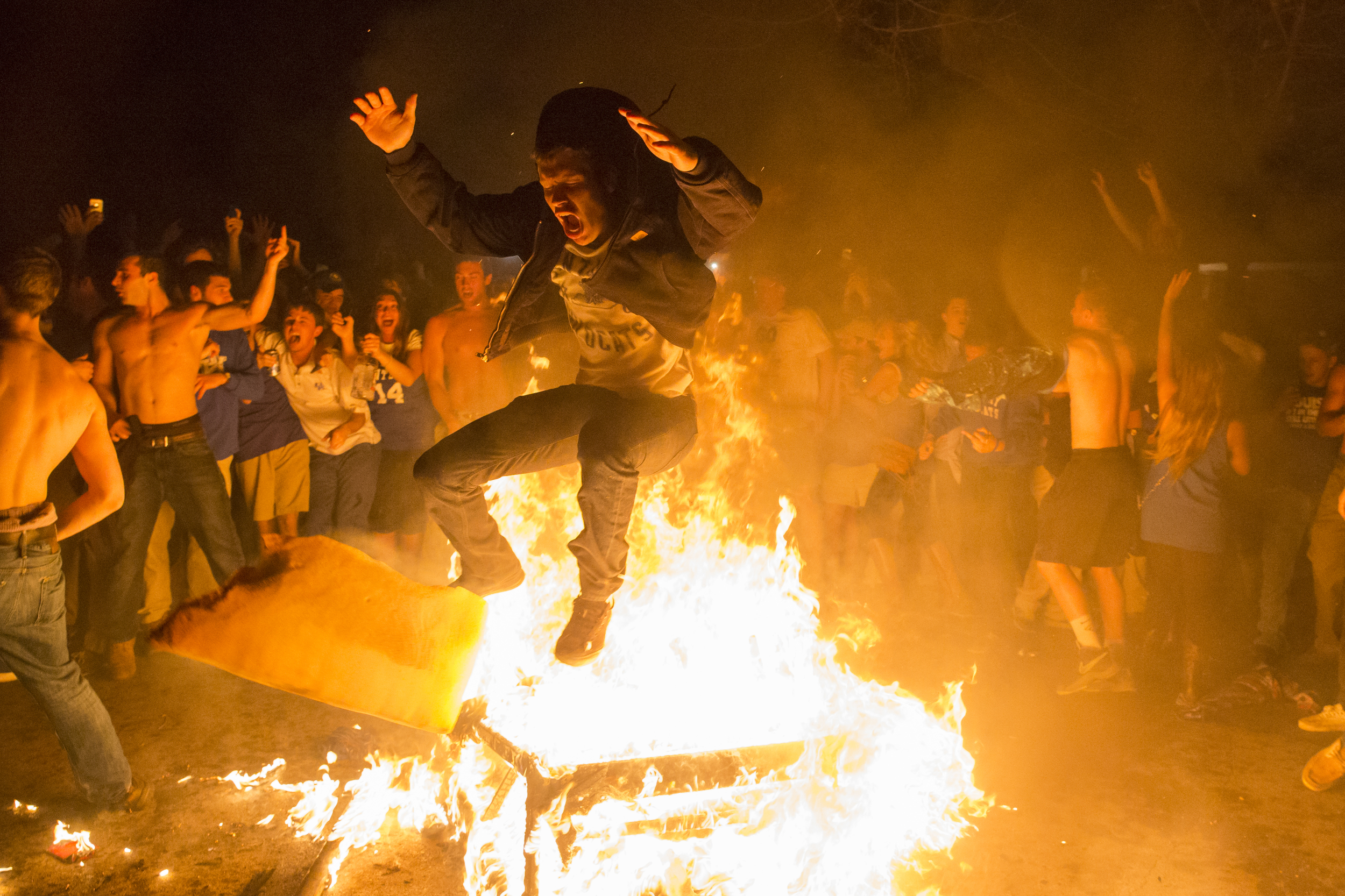 A man jumps over a burning couch on University Avenue as thousands of fans stormed State Street and University Avenue after The University Kentucky beat the The University of Louisville in Lexington, Ky. on Friday, March 28, 2014.