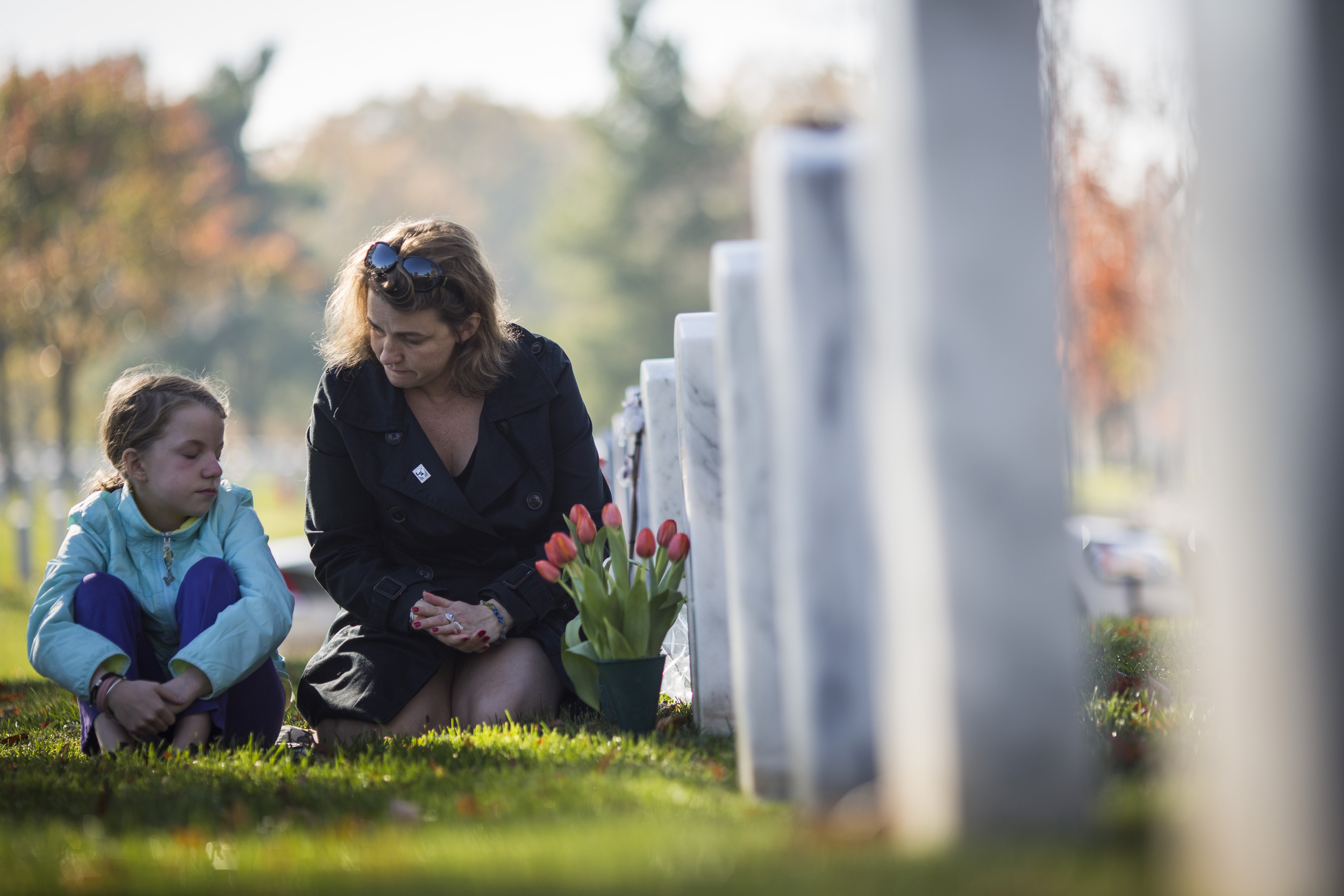 Stephanie Shain and her daughter Mia Roberts, 10, visit the grave of Shain's father, Robert George Shain a LTC in the U.S. Army who served in Vietnam and died on April 29, 2012, on Veterans Day at Arlington National Cemetery in Washington, DC on Tuesday November 11, 2014.
