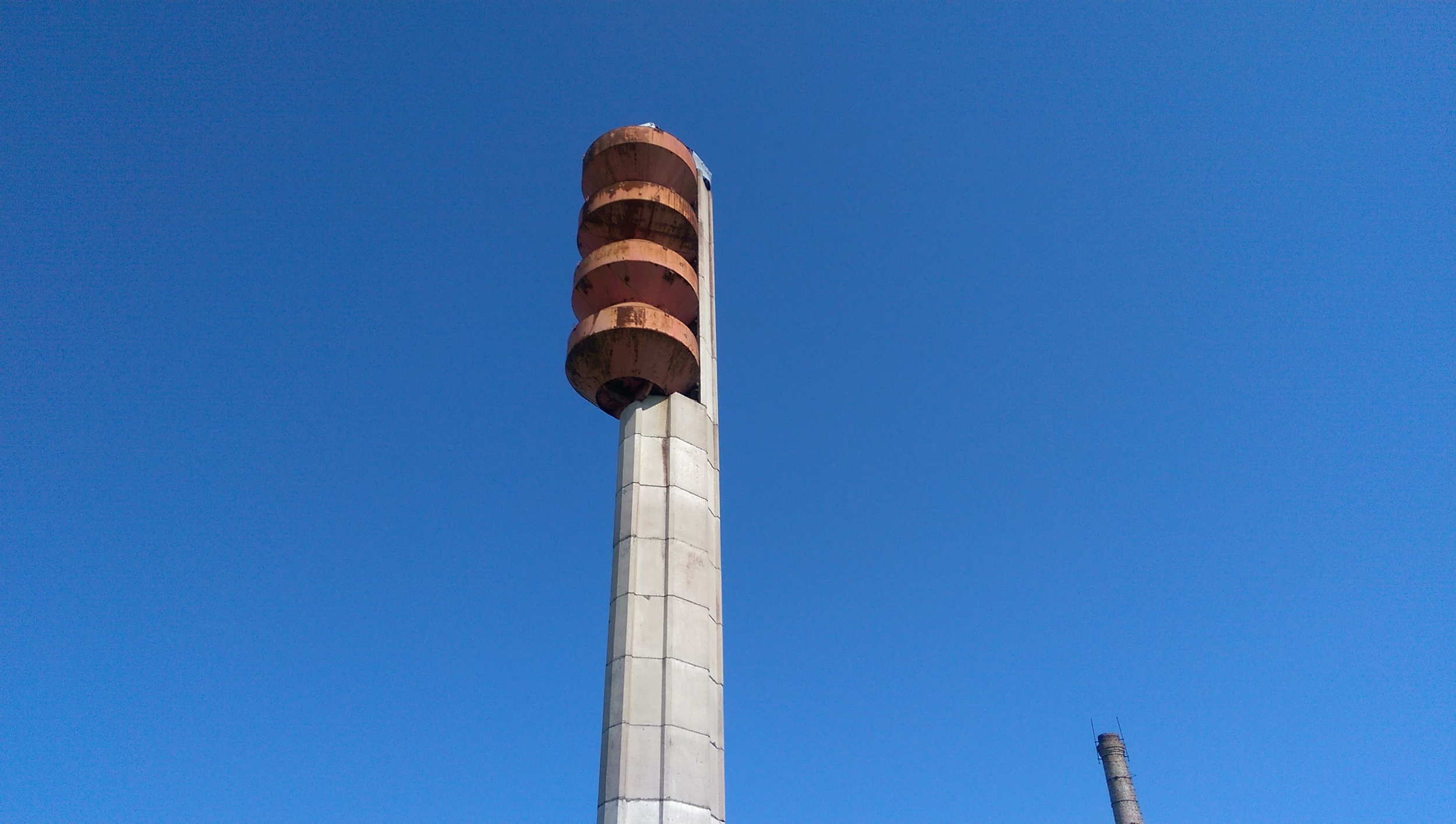 View of the top half of tower. The paint is usefully about the same colour as the rust, but fresh paint is called for at sometime which will be fun on the trapese. The steel water containers can be climbed down into via internal ladders from the top, though these have yet to be explored. The water bearing steel containers balance on a small concrete step so that centre of gravity transmits down the tower walls whilst looking ever so slightly improbable.